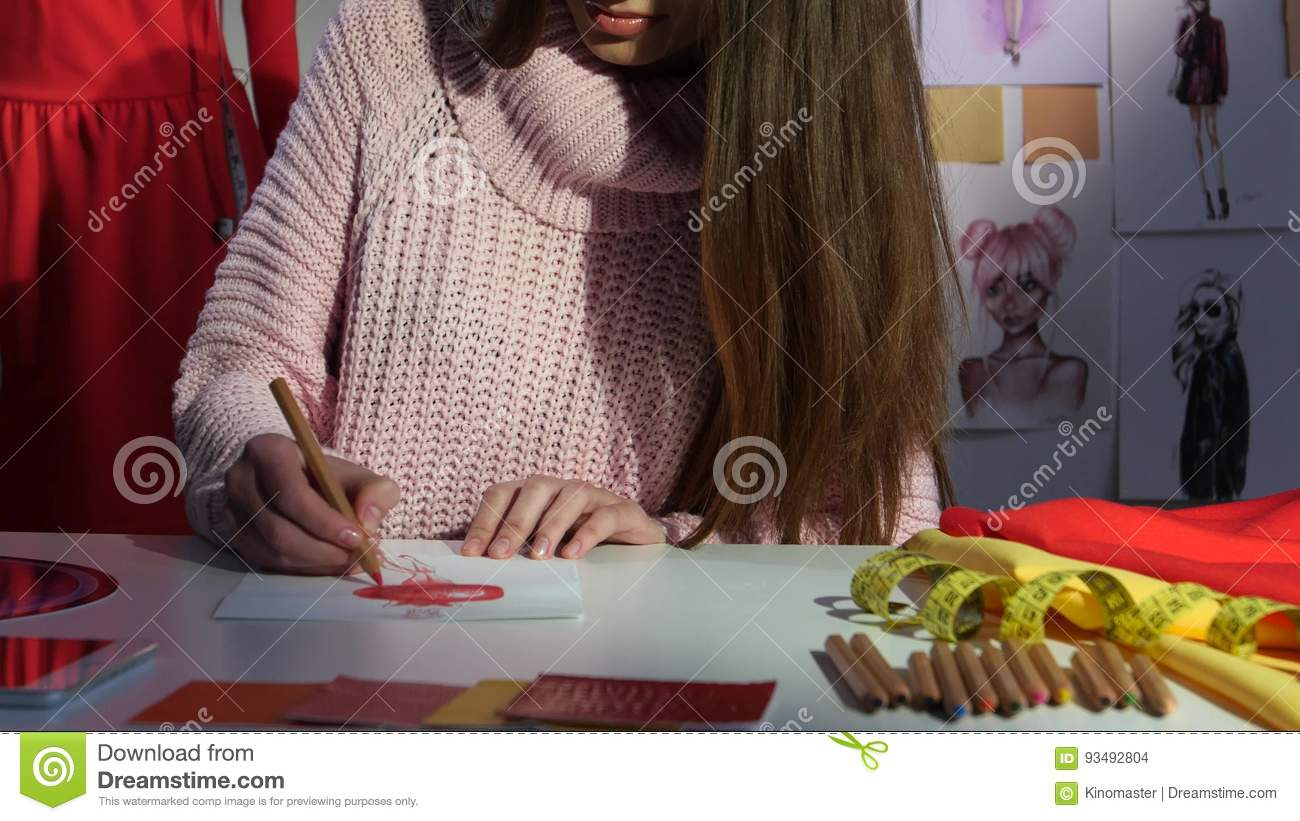 Designer Draws A Sketch Of A Red Dress On A Mannequin Hangs A