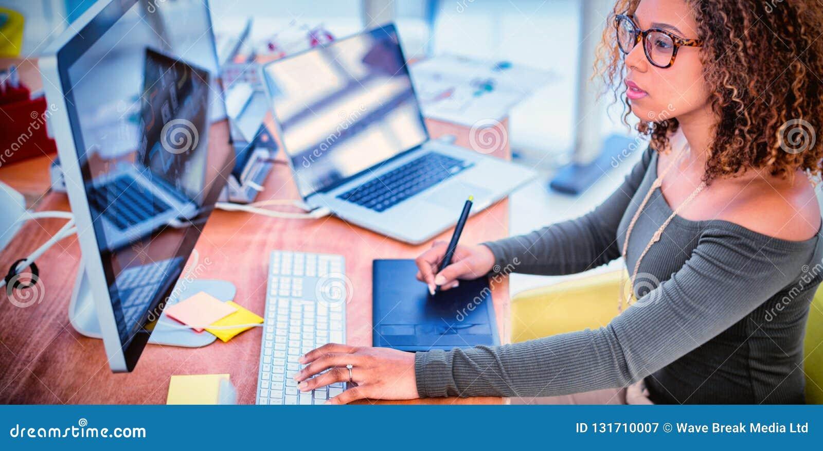 Designer gráfico fêmea que trabalha no computador ao usar a tabuleta gráfica na mesa