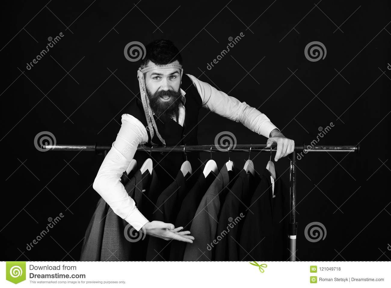 Designer leans on clothes hangers. Man with beard in vest