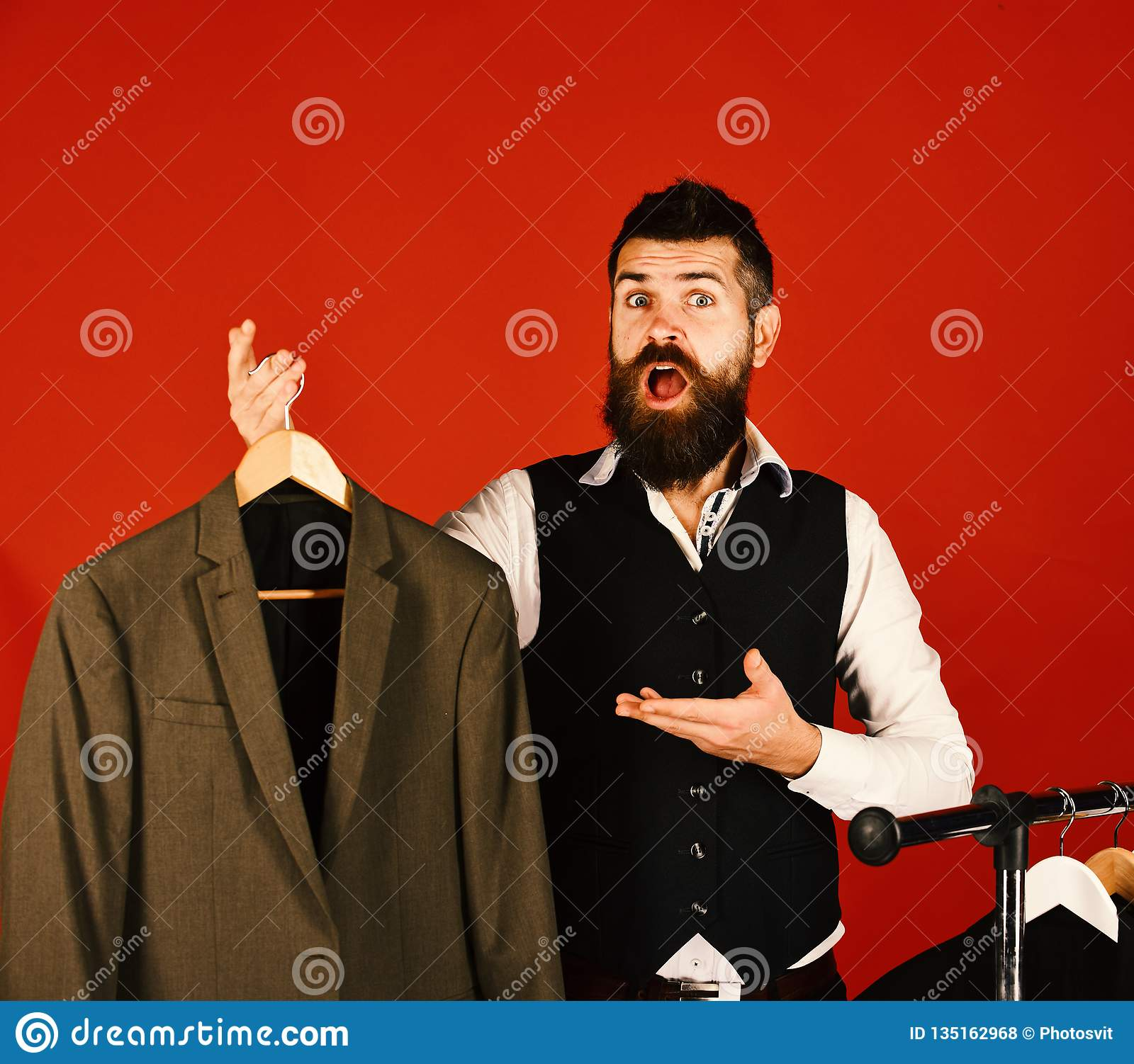 Designer and suit on clothes hanger. Man with beard