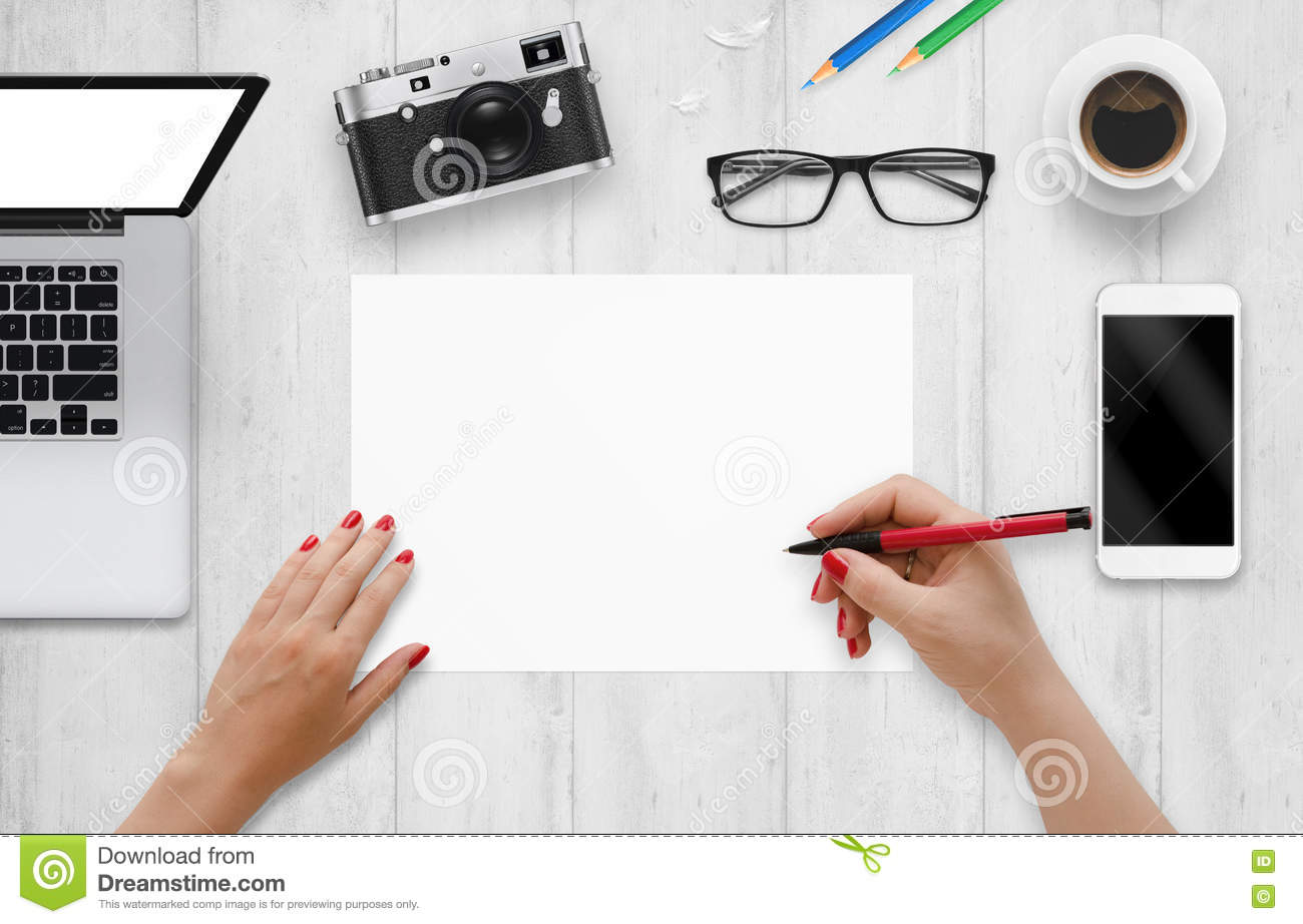 designer writes on a blank paper top view of work desk with