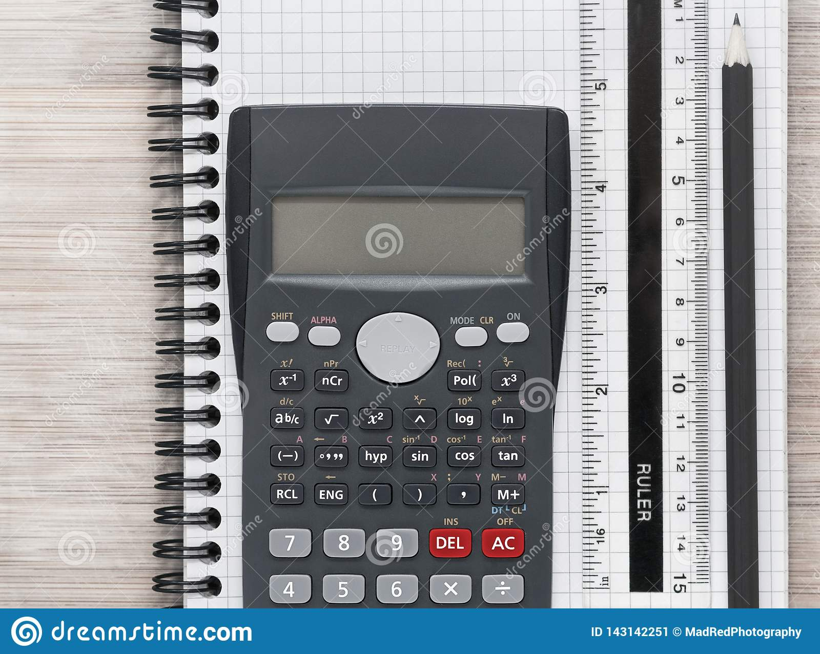 Desk flat lay with calculator, ruler and pencil on a notebook