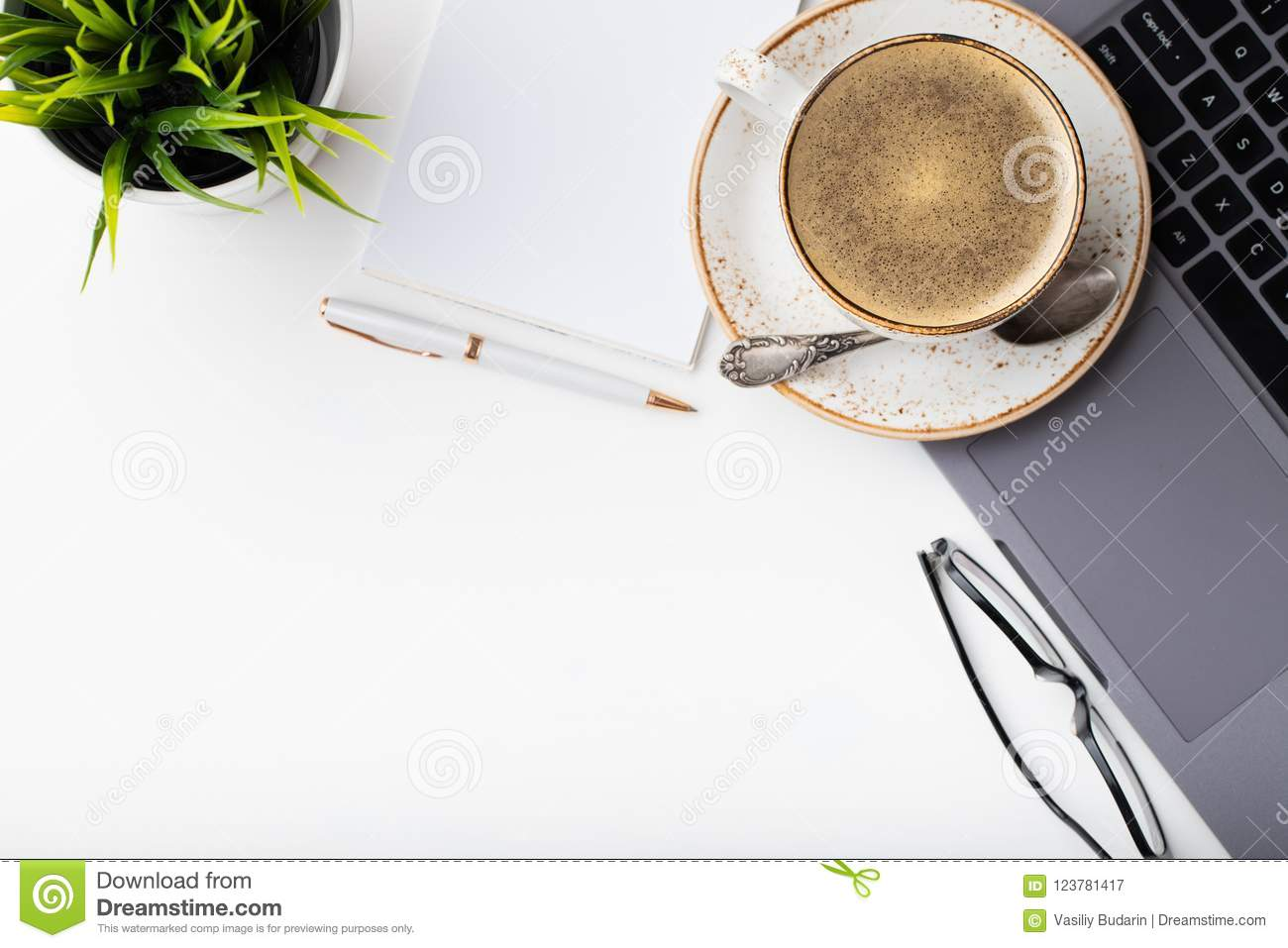 Desk with laptop, eye glasses, notepad, pen and a cup of coffee on a white table. Top view with copy space. Flat lay. Light backgr
