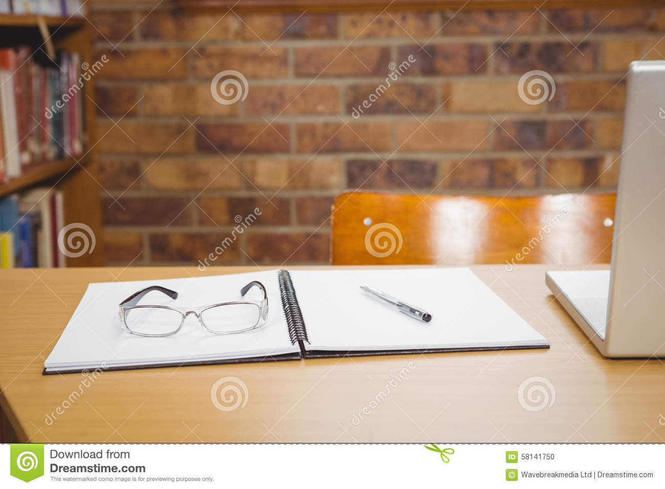 Desk with laptop, glasses and ledger on it