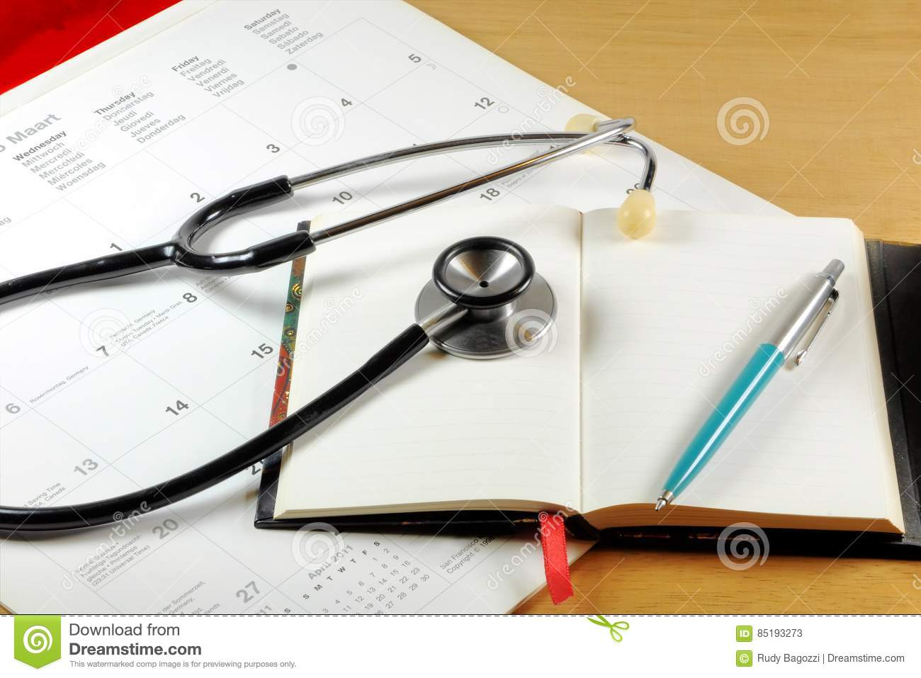 A Desk Top With Stethoscope, Notebook, Pen And Calendar