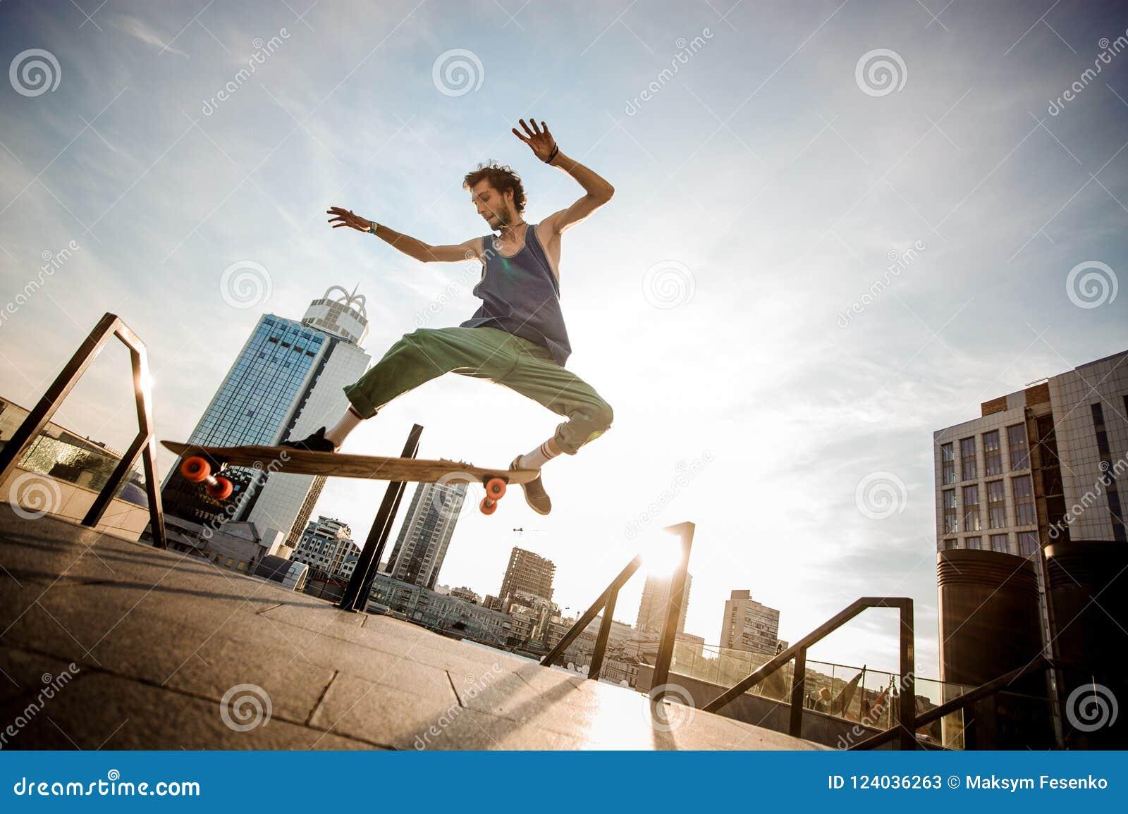 Deskorolkarz skacze na pokładzie miasto budynków na lato d przeciw