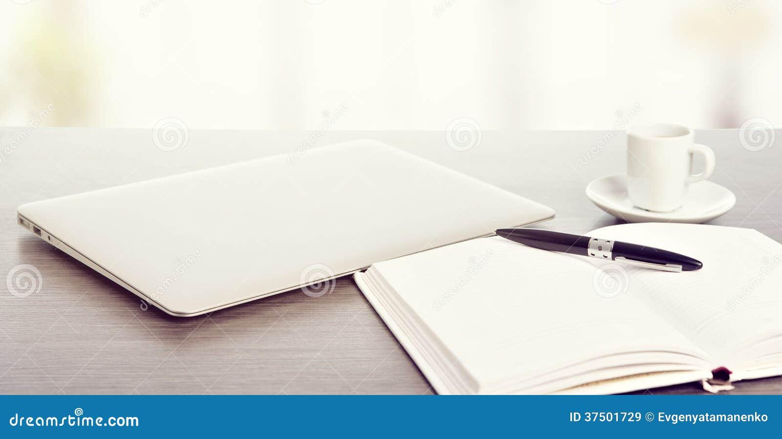 Desktop biuro. Laptop, kawa, notatnik i pióro,