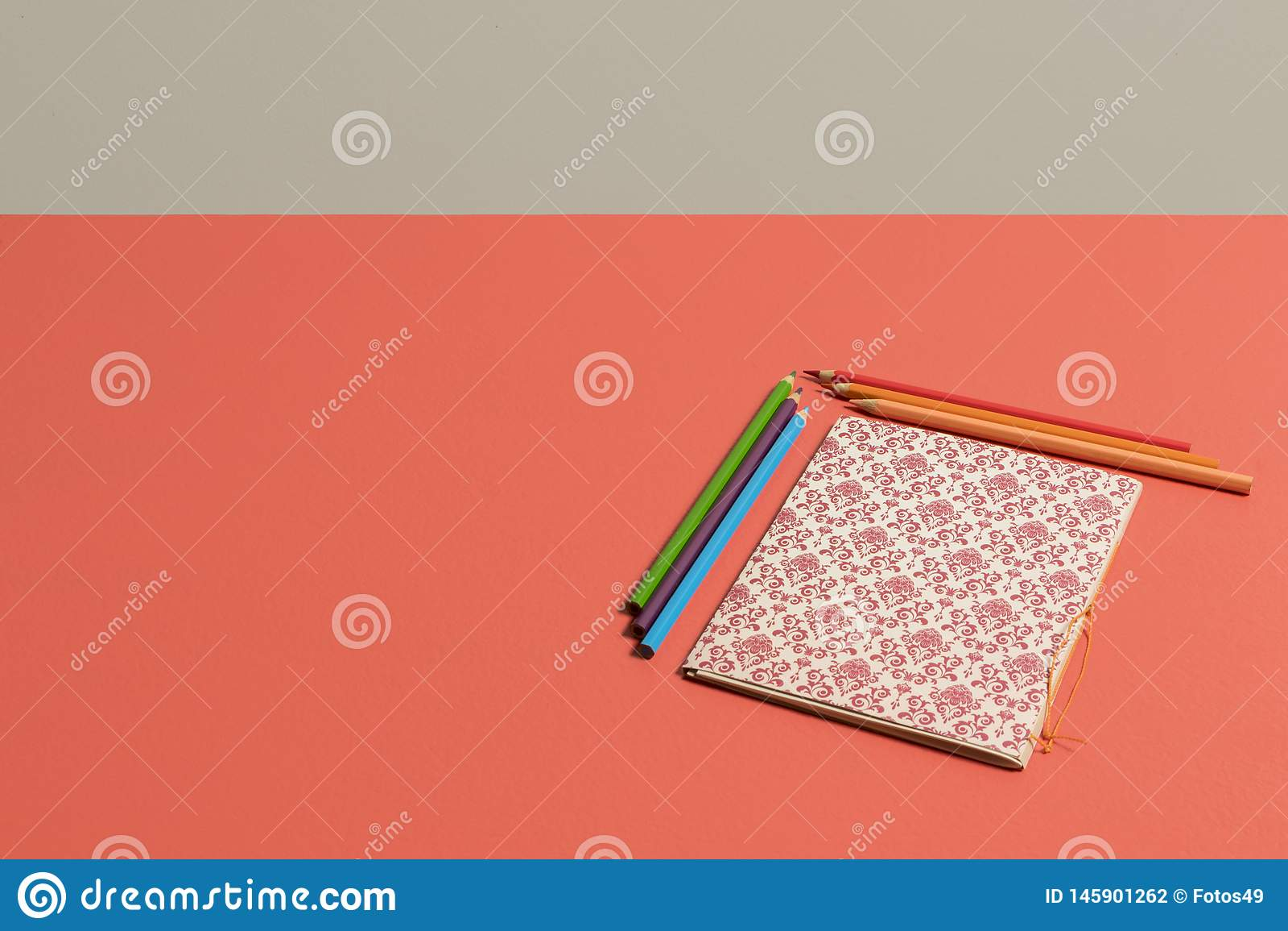 Desktop no coral vívido com o caderno nos lápis do canto e da cor