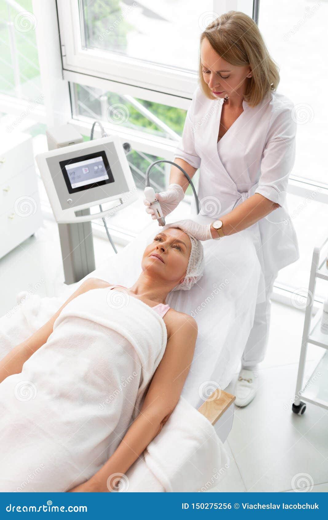 Deskundige cosmetologist die van Nice een gezichts het reinigen procedure doen