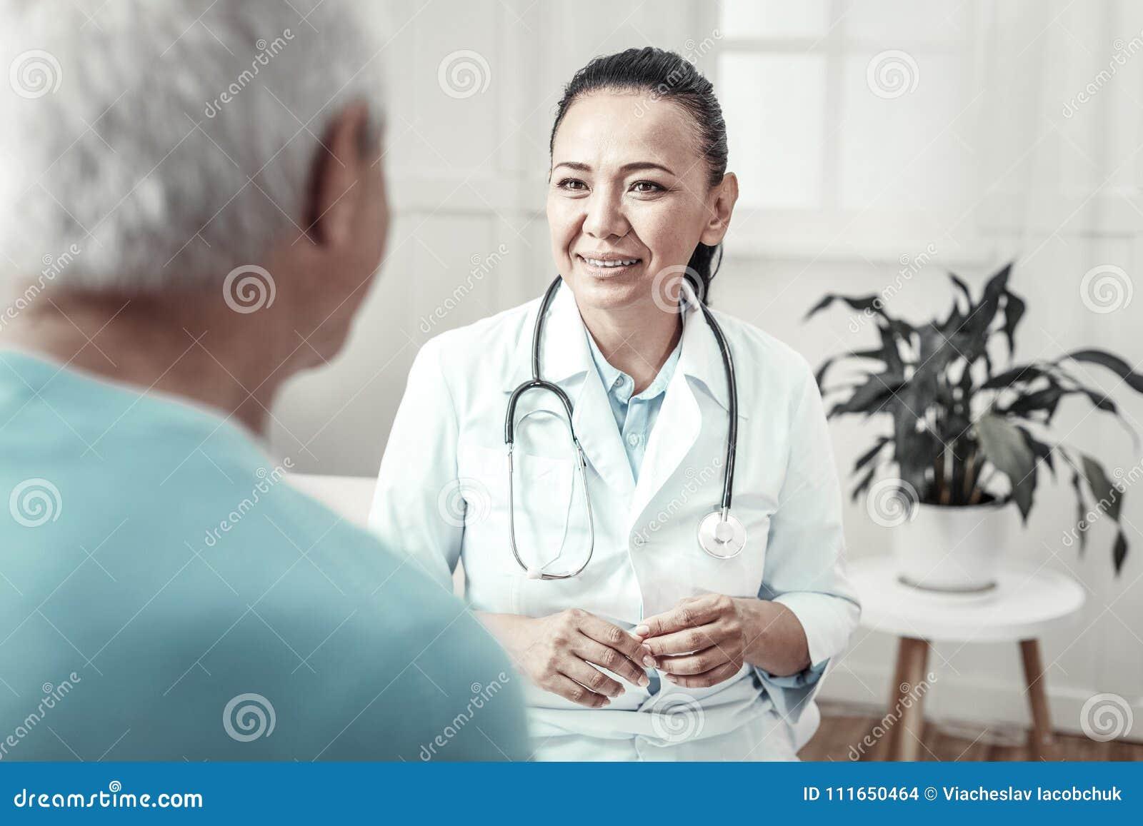 Deskundige leuke verpleegster die en overleg glimlachen hebben