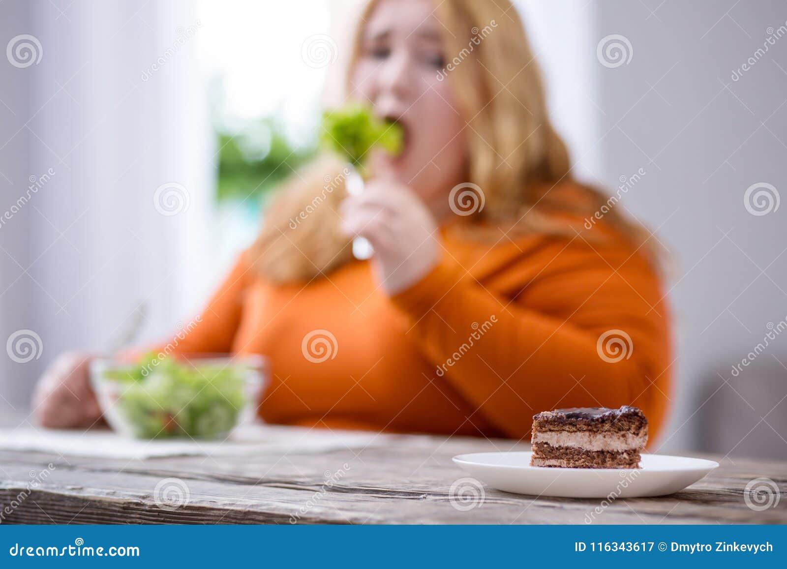 Desolate plump woman looking at cookies