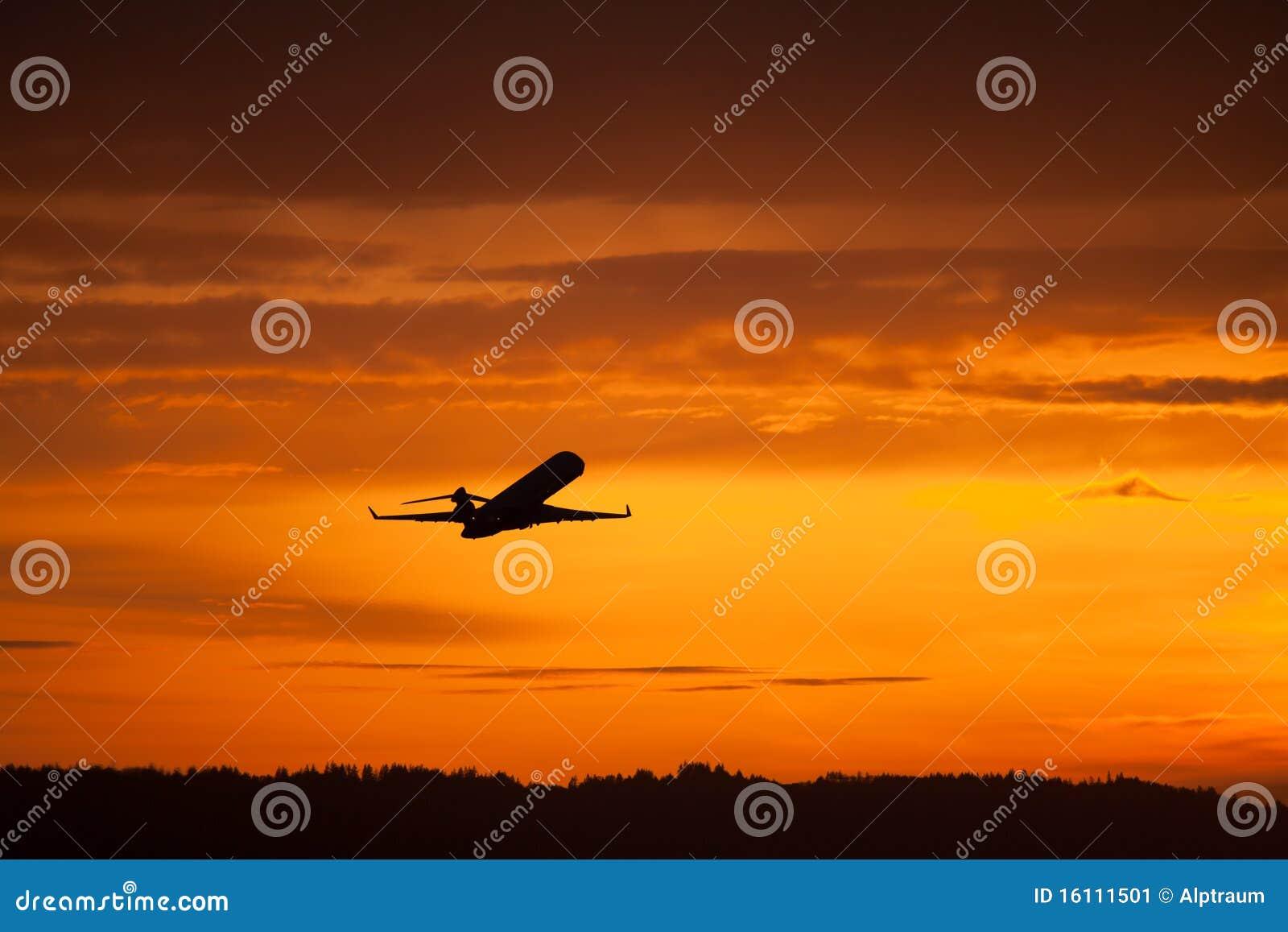 Despegue del aeroplano en puesta del sol