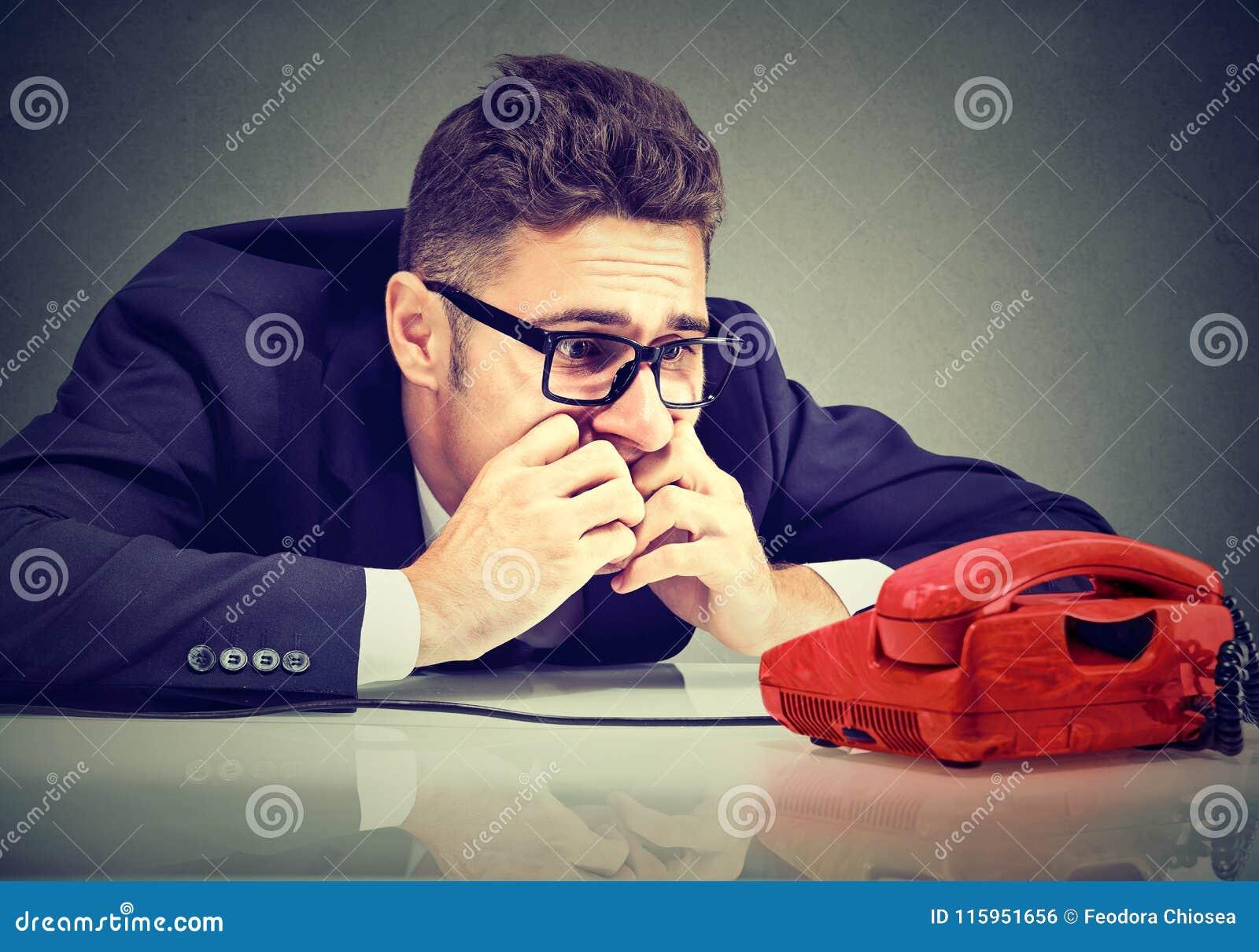 Desperat affärsman som väntar på någon att kalla honom