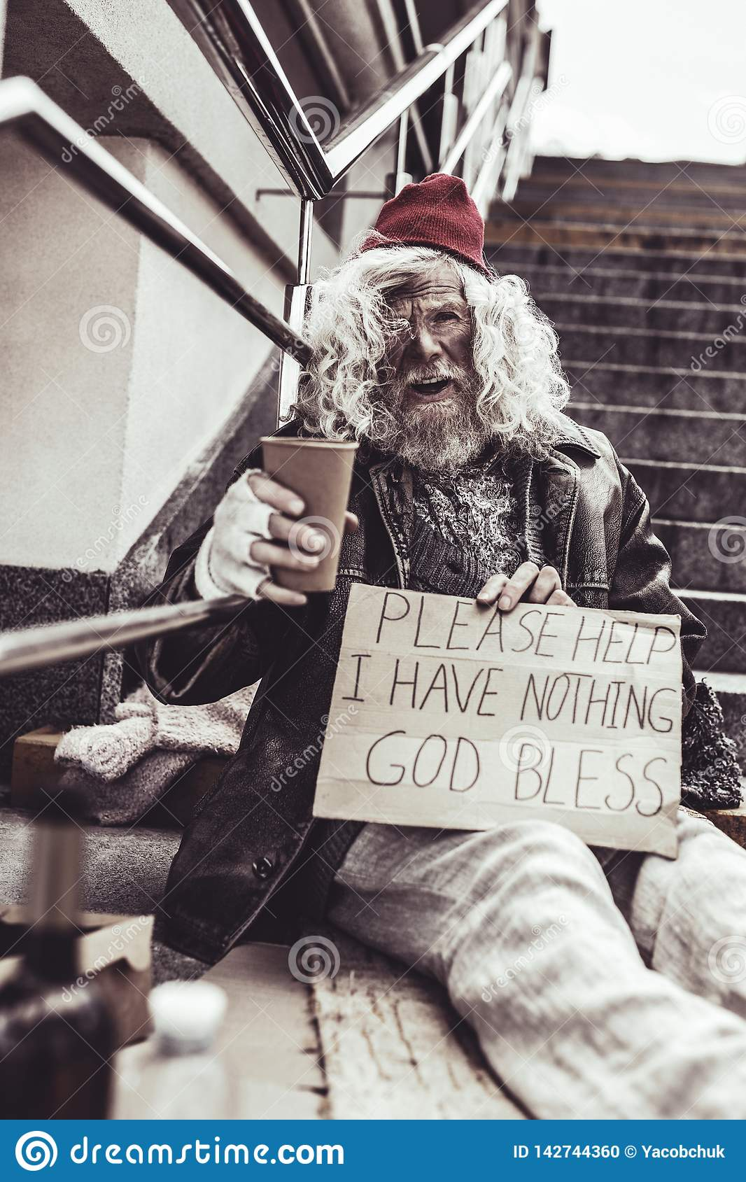 Desperate beggar sitting outside and writing poster asking for help.