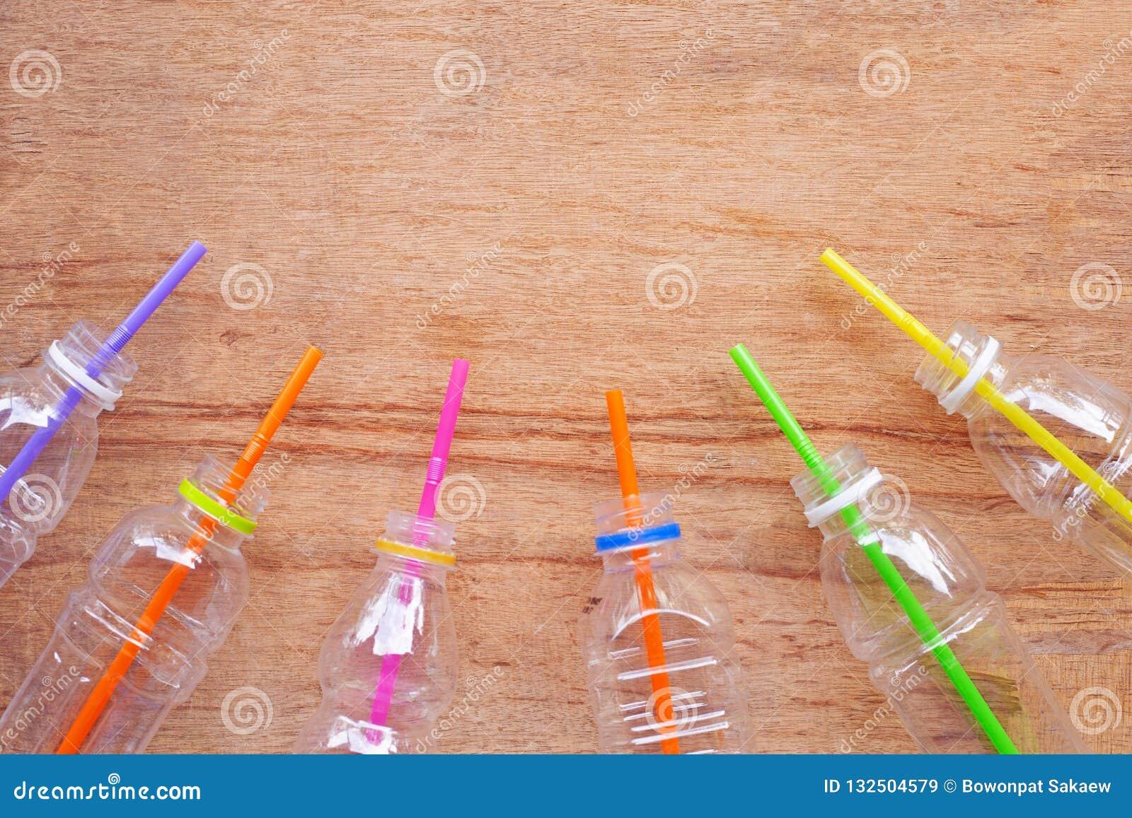 Desperdício plástico, garrafas plásticas com palhas