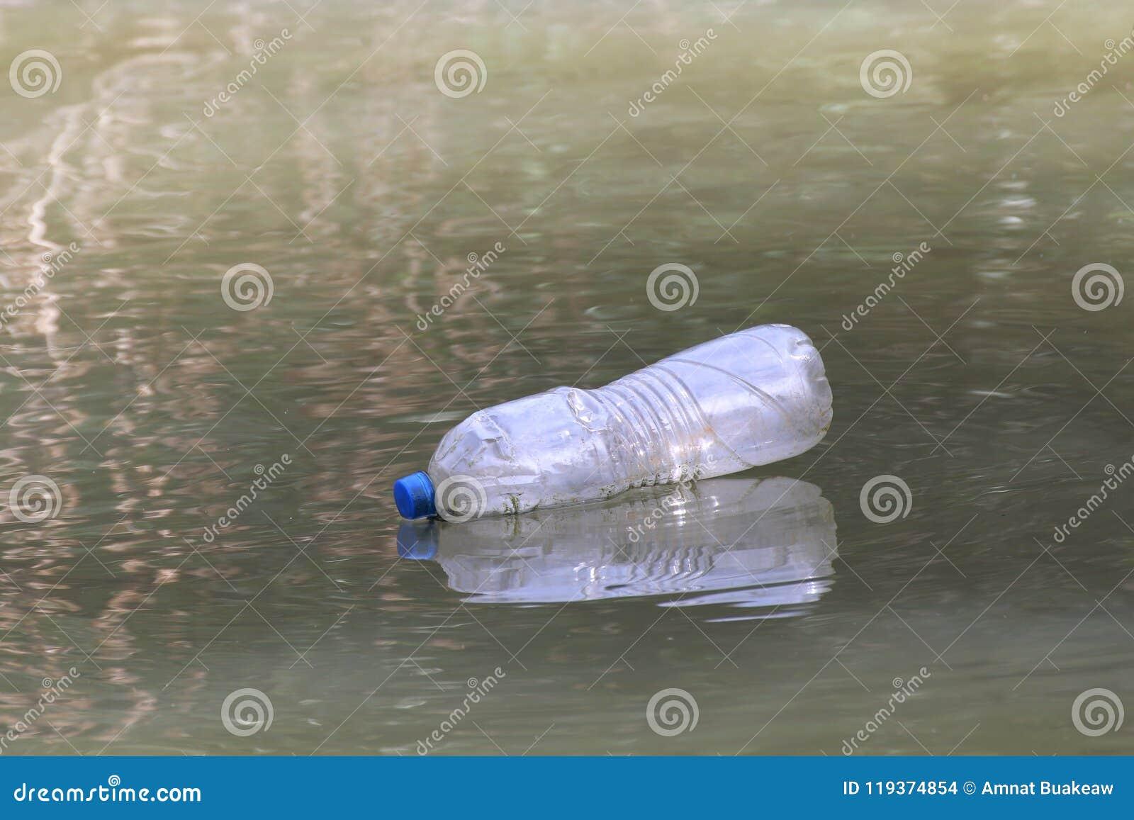 Desperdício plástico na superfície da água suja, água podre da garrafa, desperdício da garrafa