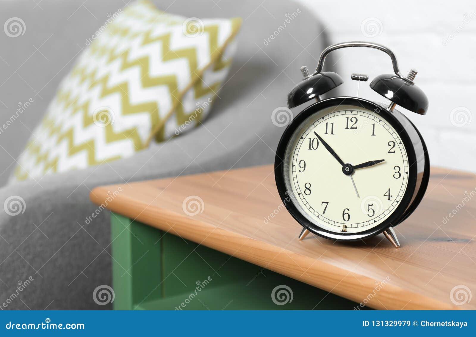 Despertador análogo na tabela lateral na sala de visitas, espaço para o texto