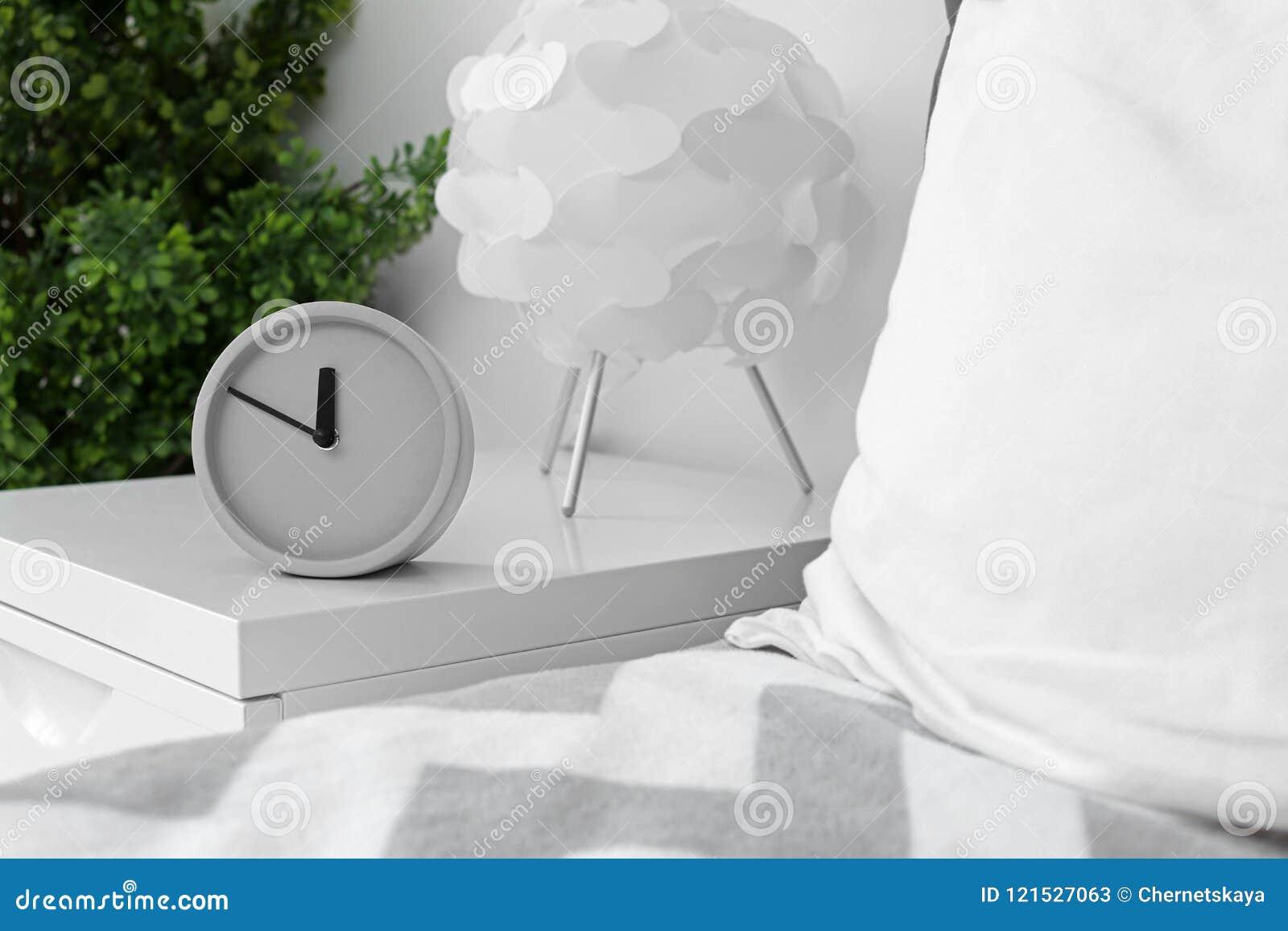 Despertador análogo na tabela no quarto