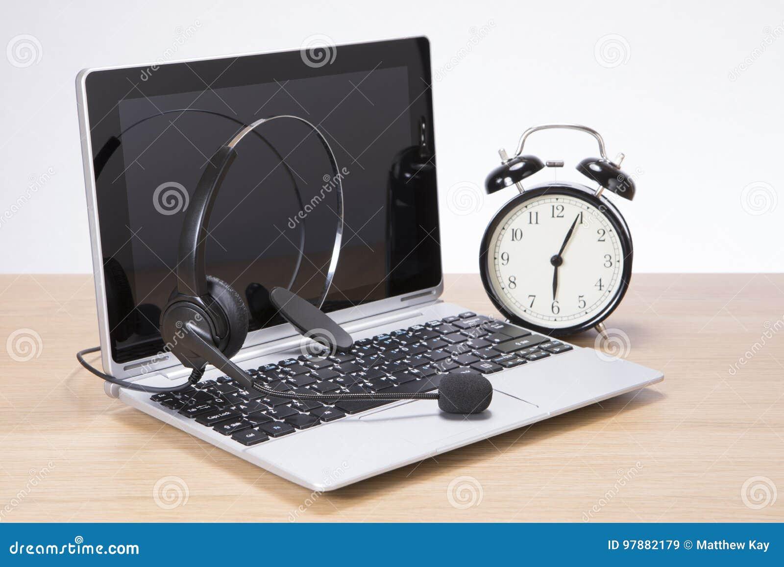 Despertador ao lado de um portátil e de uns auriculares
