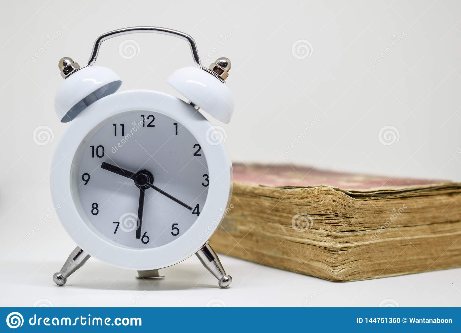 Despertador blanco y libro viejo ( Dictionary) en el fondo blanco