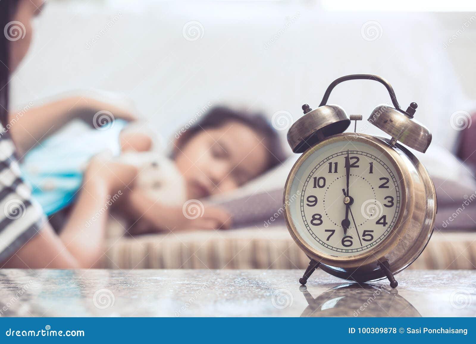 Despertador del vintage en el fondo de la madre que toma al niño del cuidado