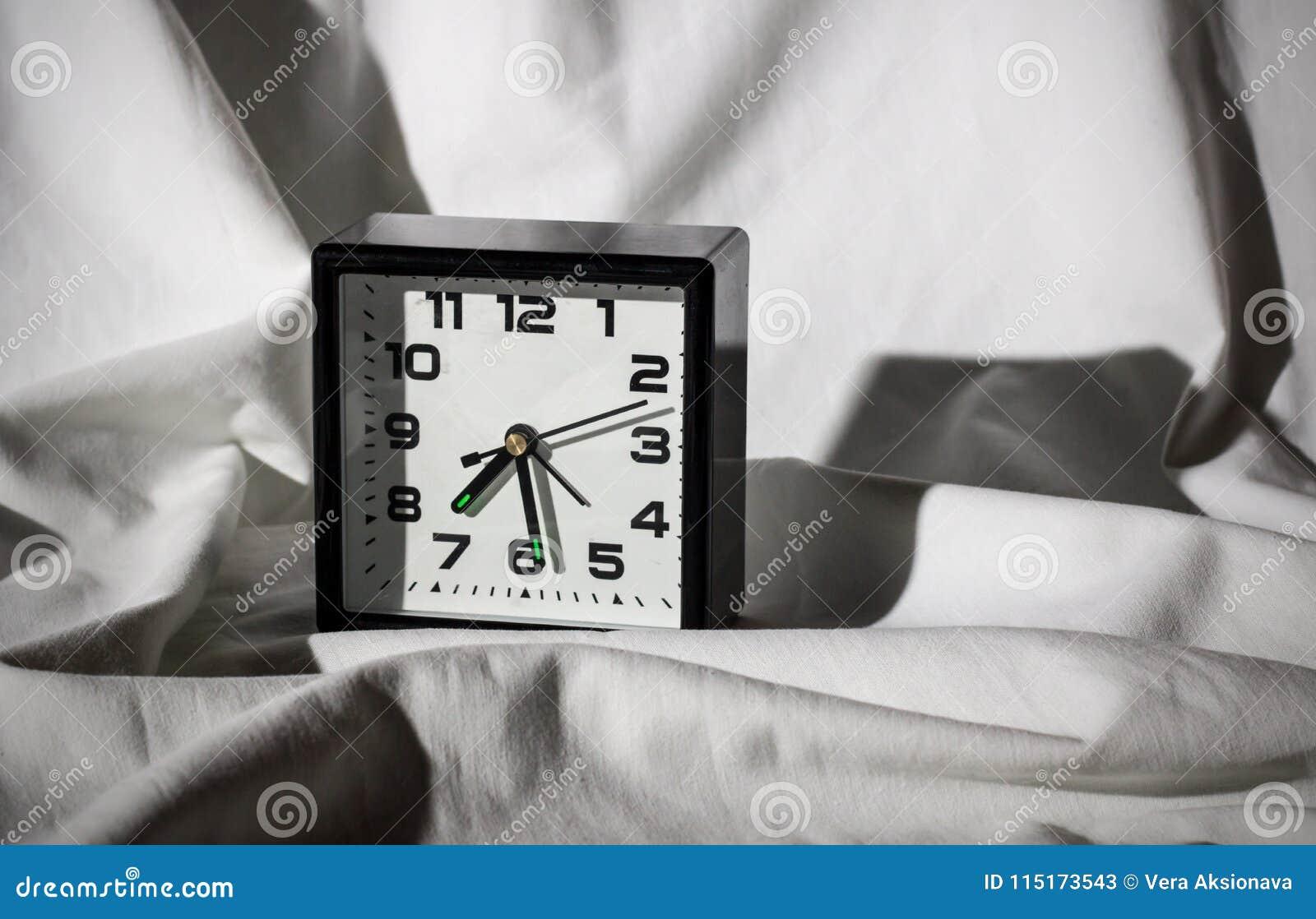 Despertador preto em uma folha branca com sombras duras