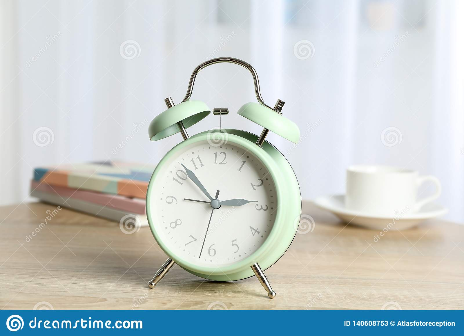 Despertador retro bonito com xícara de café, livros na tabela