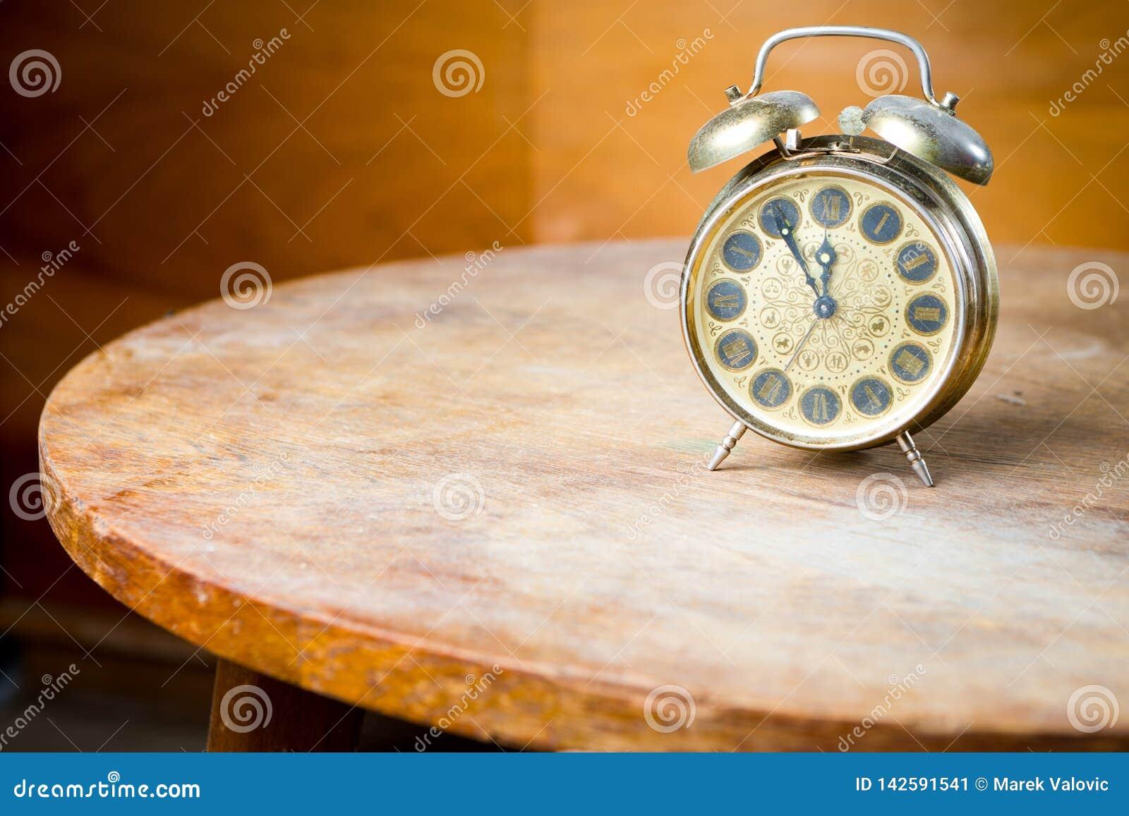 Despertador usado viejo en la mesa redonda Tecnología obsoleta pero gran diseño - cinco a doce