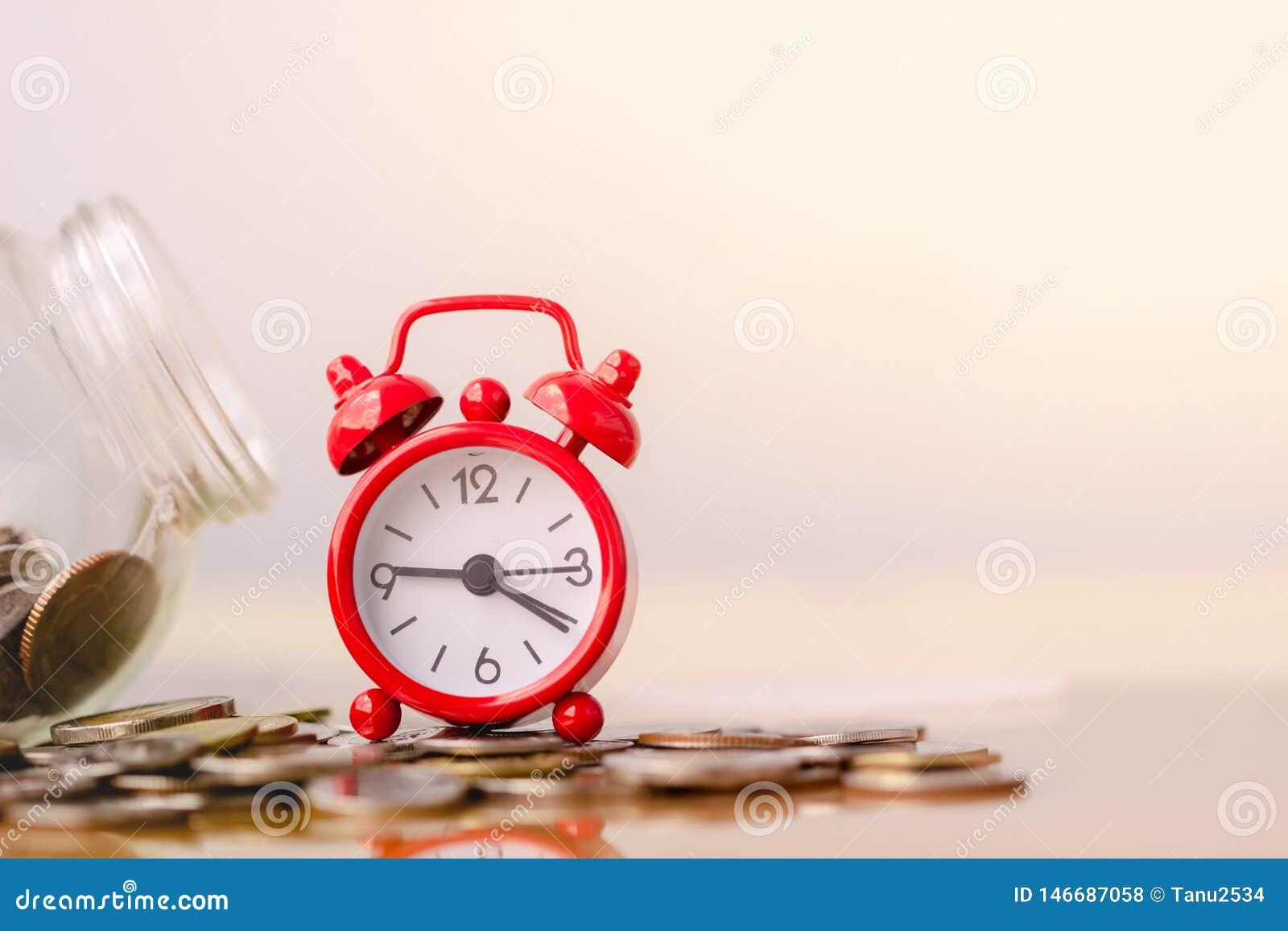 Despertador vermelho na pilha de moedas no conceito das economias e do crescimento do dinheiro ou das economias da energia Concei