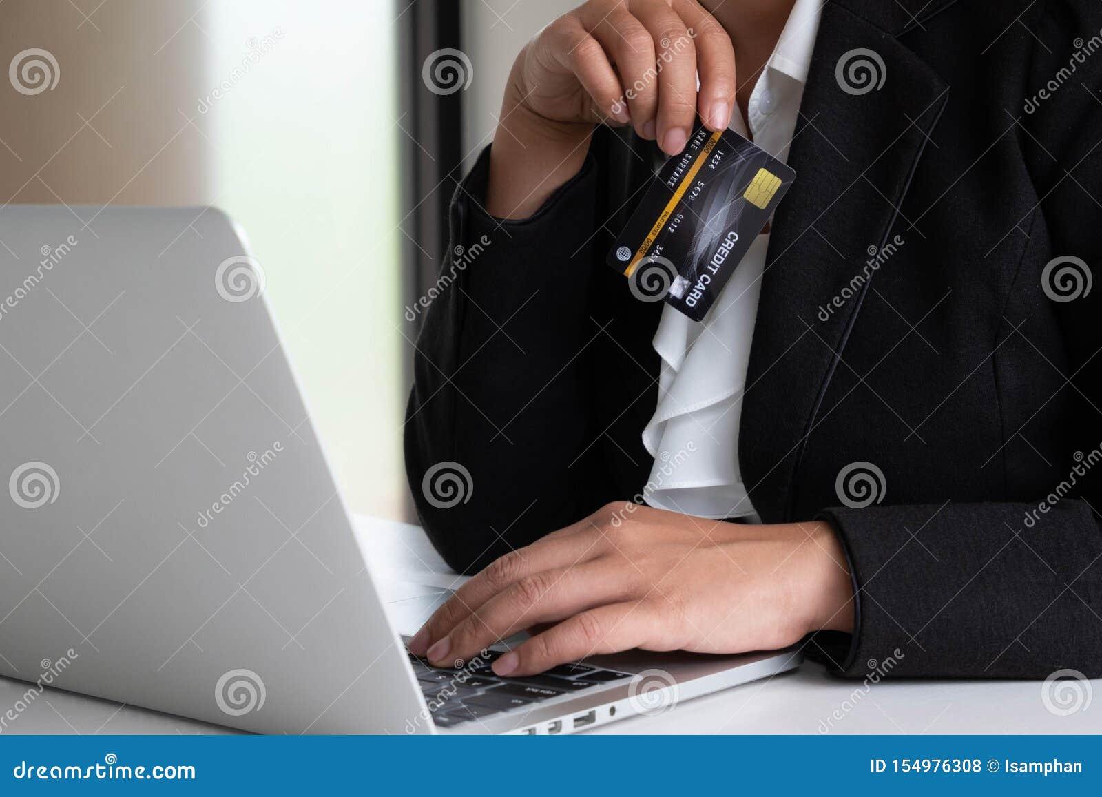 Despesas de consumo da mulher de negócio através do cartão de crédito para a compra em linha em seu portátil