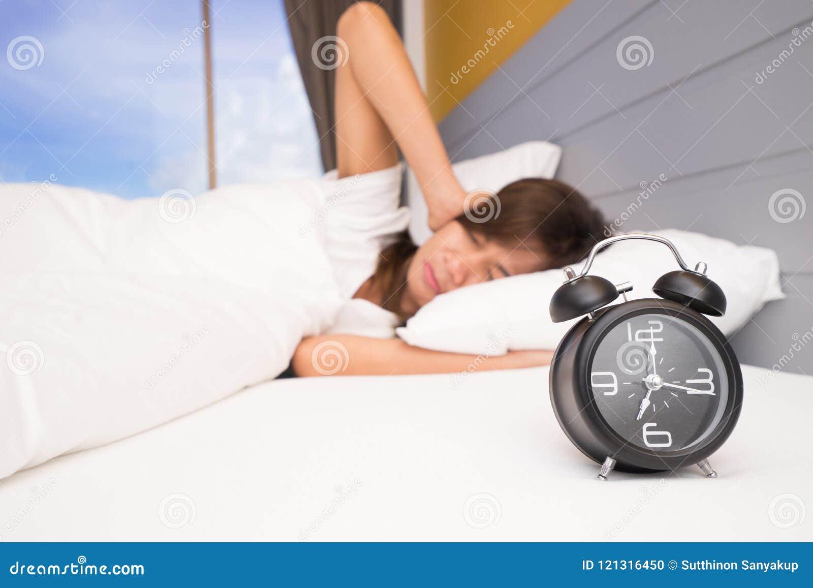 Despierte, mujer asiática en mano que extiende de la cama al despertador la muchacha apaga el despertador que despierta por la ma