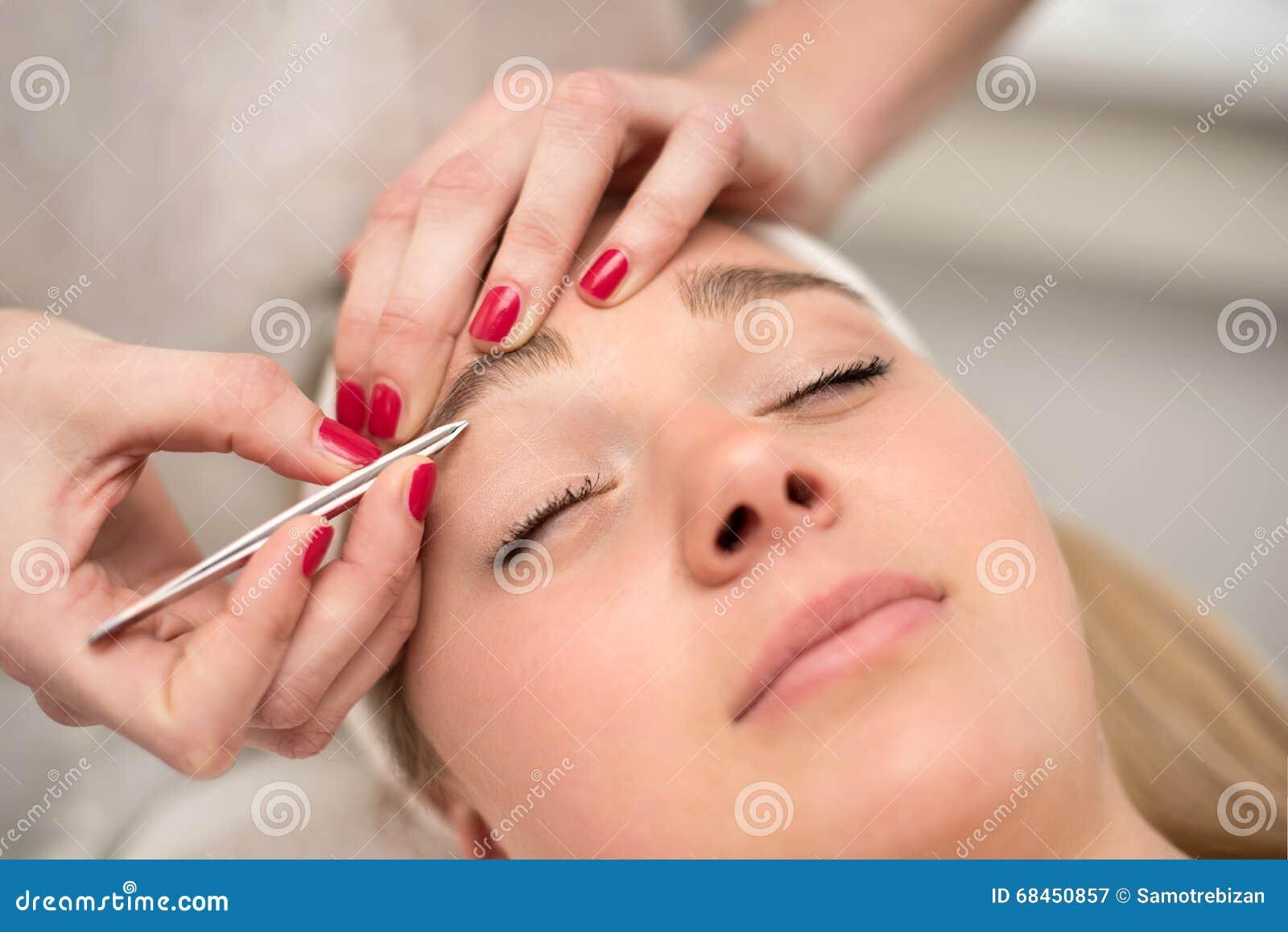 Desplume de las cejas con las pinzas del cosmetólogo en salón de belleza