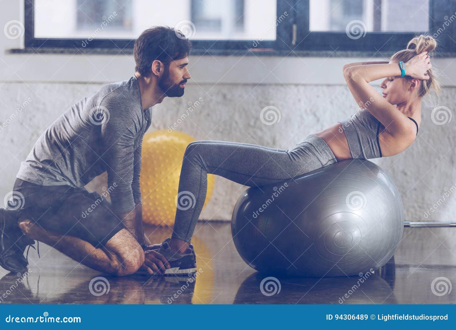 Desportista novo atlético que faz o Abs na bola da aptidão no gym