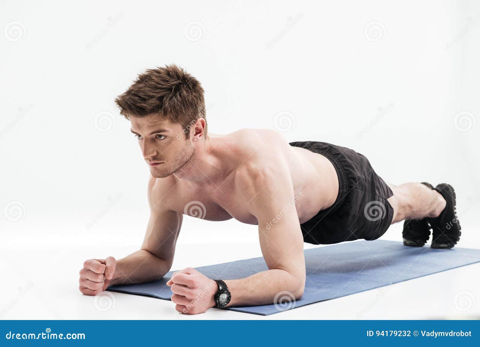 Desportista novo que faz o exercício da prancha em uma esteira da aptidão