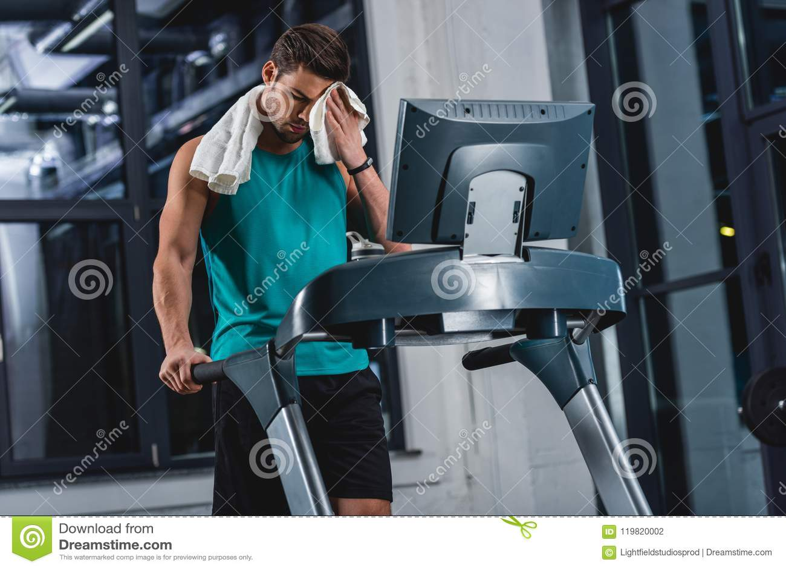 Desportista suado cansado com treinamento de toalha na escada rolante