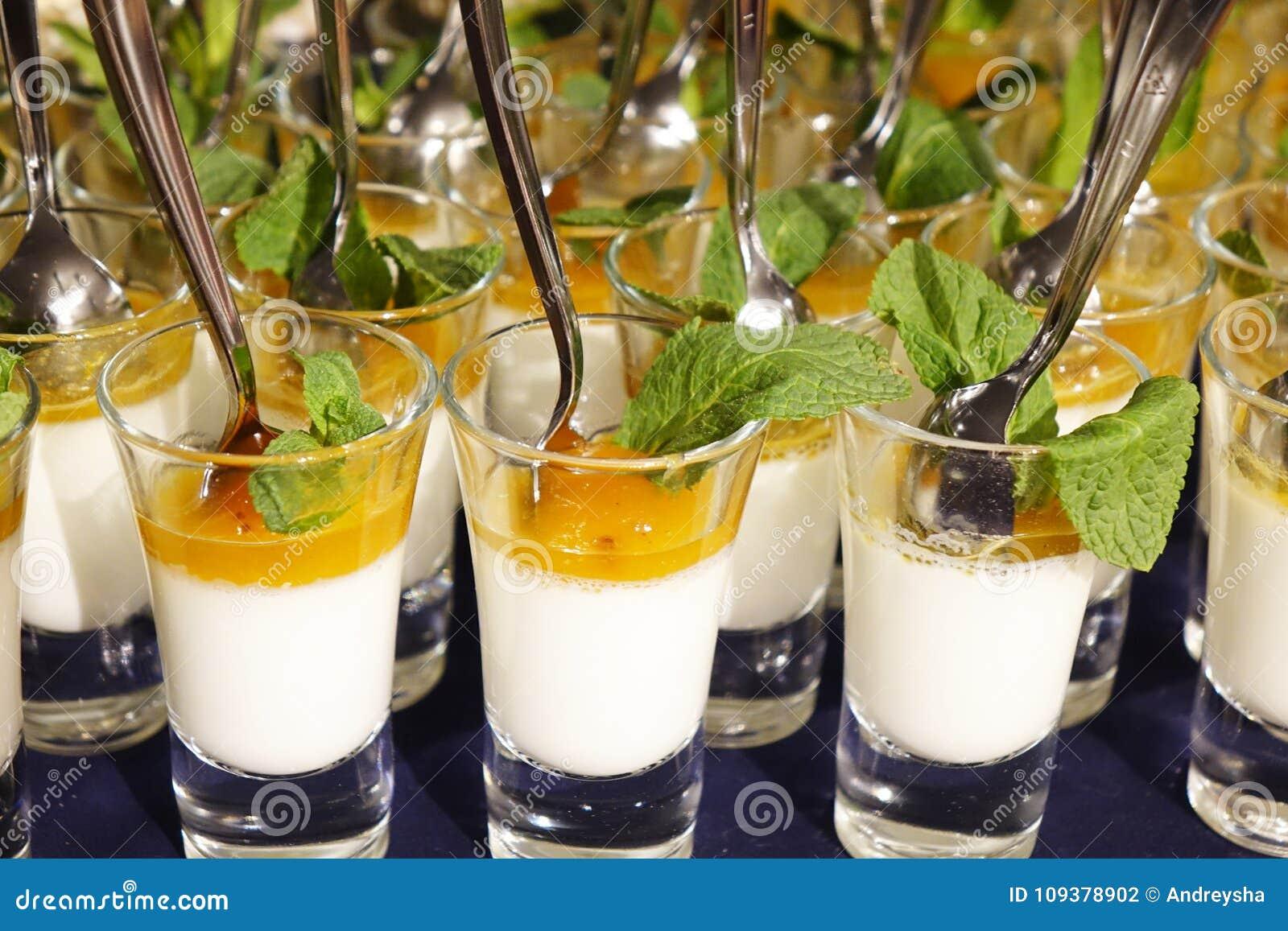 Dessert crémeux et crème glacée salée de caramel dans des pots en verre avec la menthe fraîche