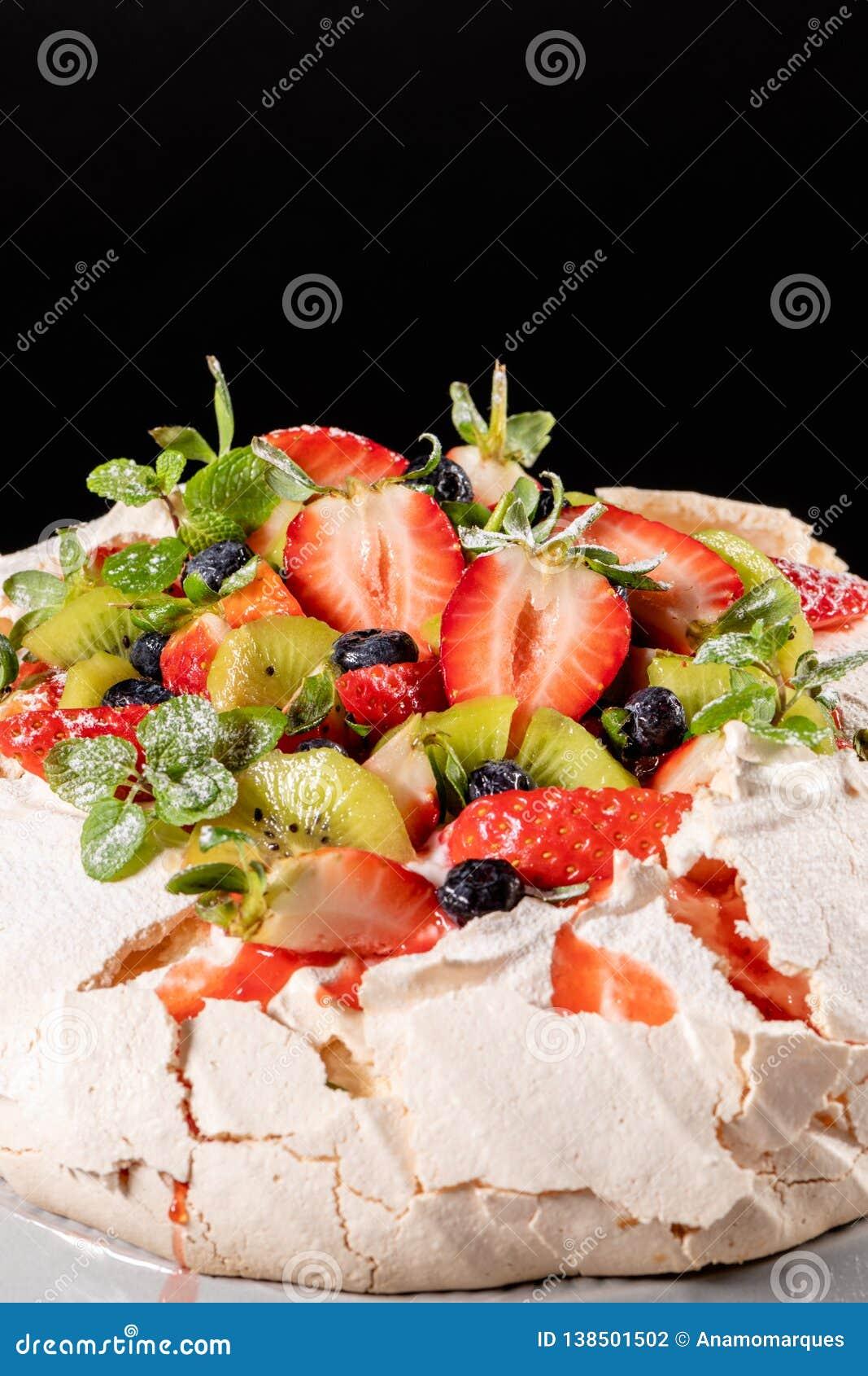 Dessert de gâteau de meringue de vacherin fait avec les fraises, le kiwi, les myrtilles et la menthe