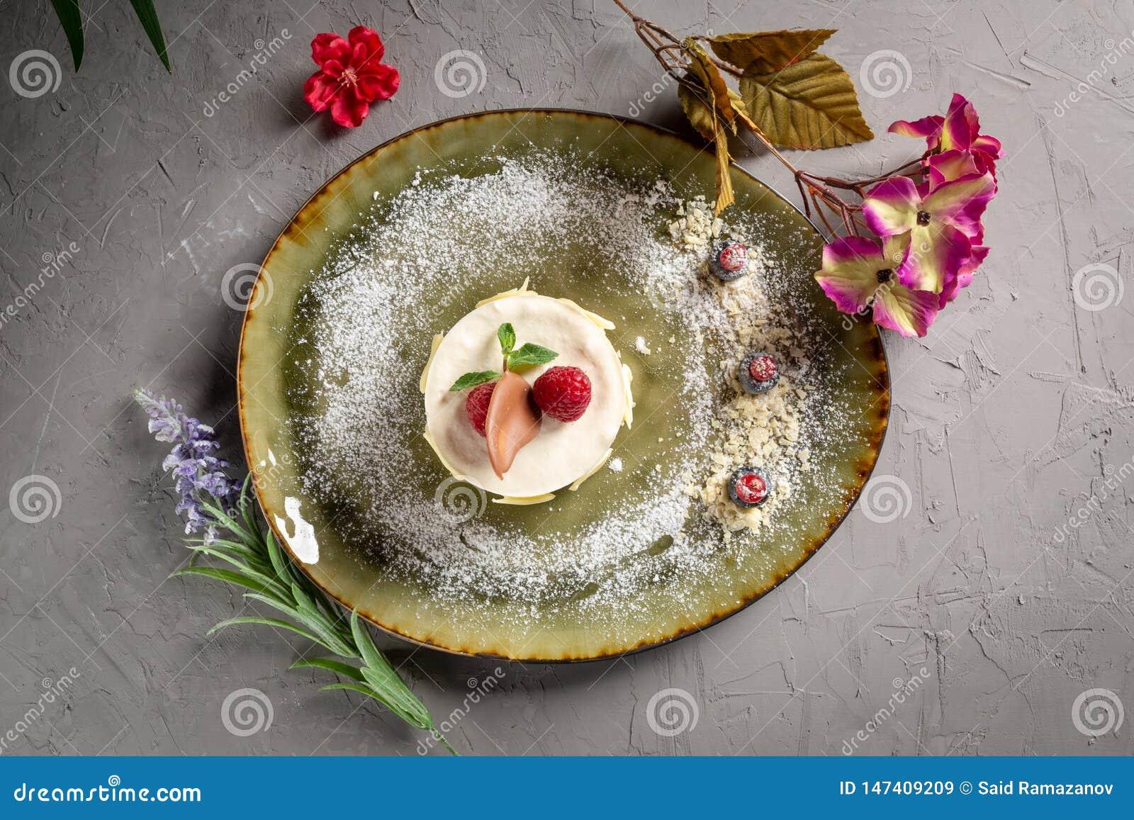 Dessert de lait avec le fruit et le chocolat sur un fond gris