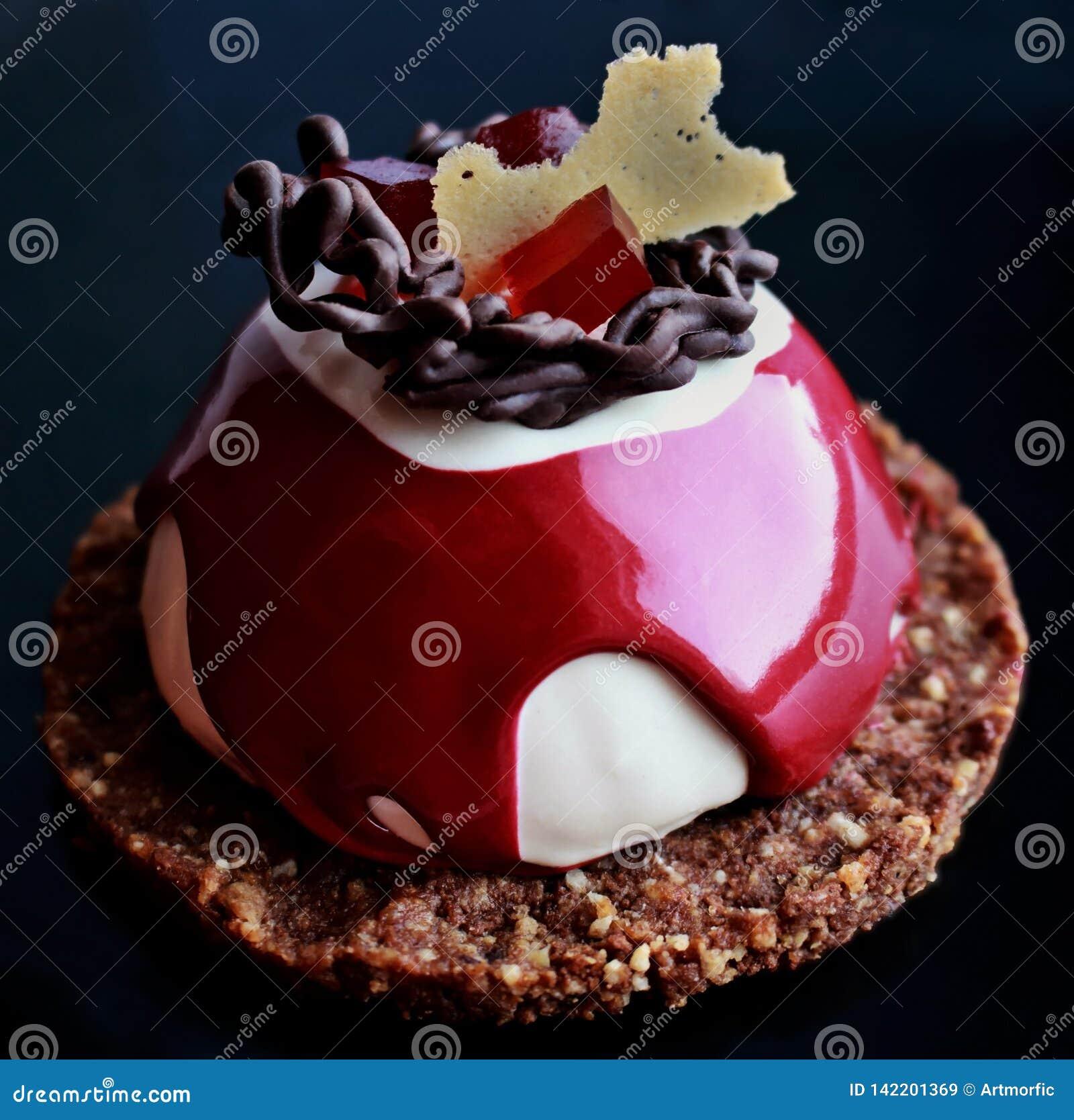 Dessert rouge et blanc avec la décoration de chocolat, la gelée rouge et la base de biscuit