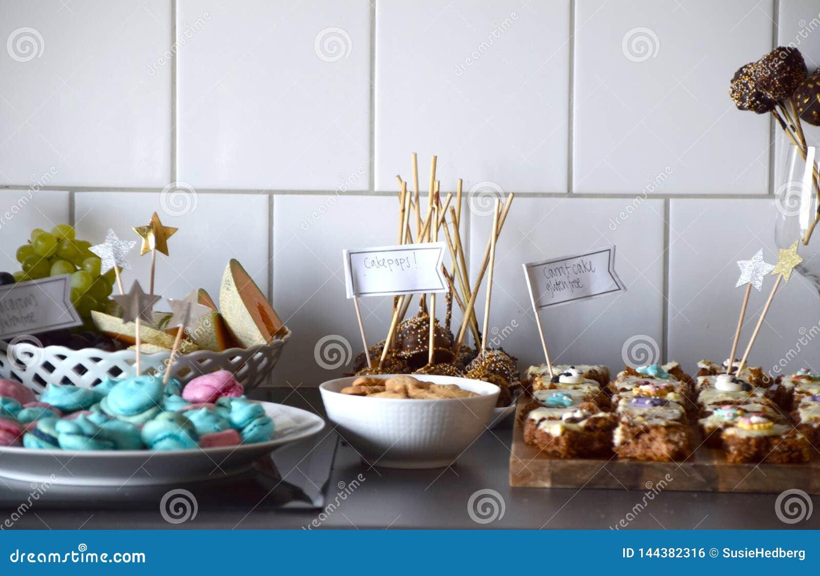 Dessertbuffet met macarons, wortelcake, koekjes en fruit