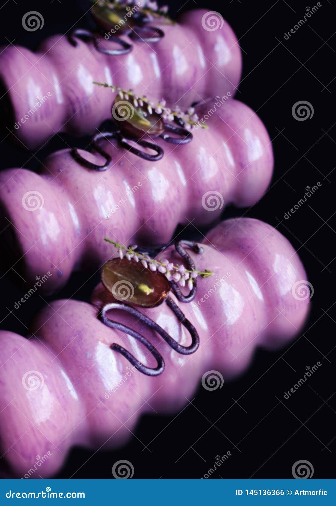 Desserts vitrés pourpres de raisin avec des raisins, les fleurs de ressort et les décorations frais de chocolat sur le fond noi