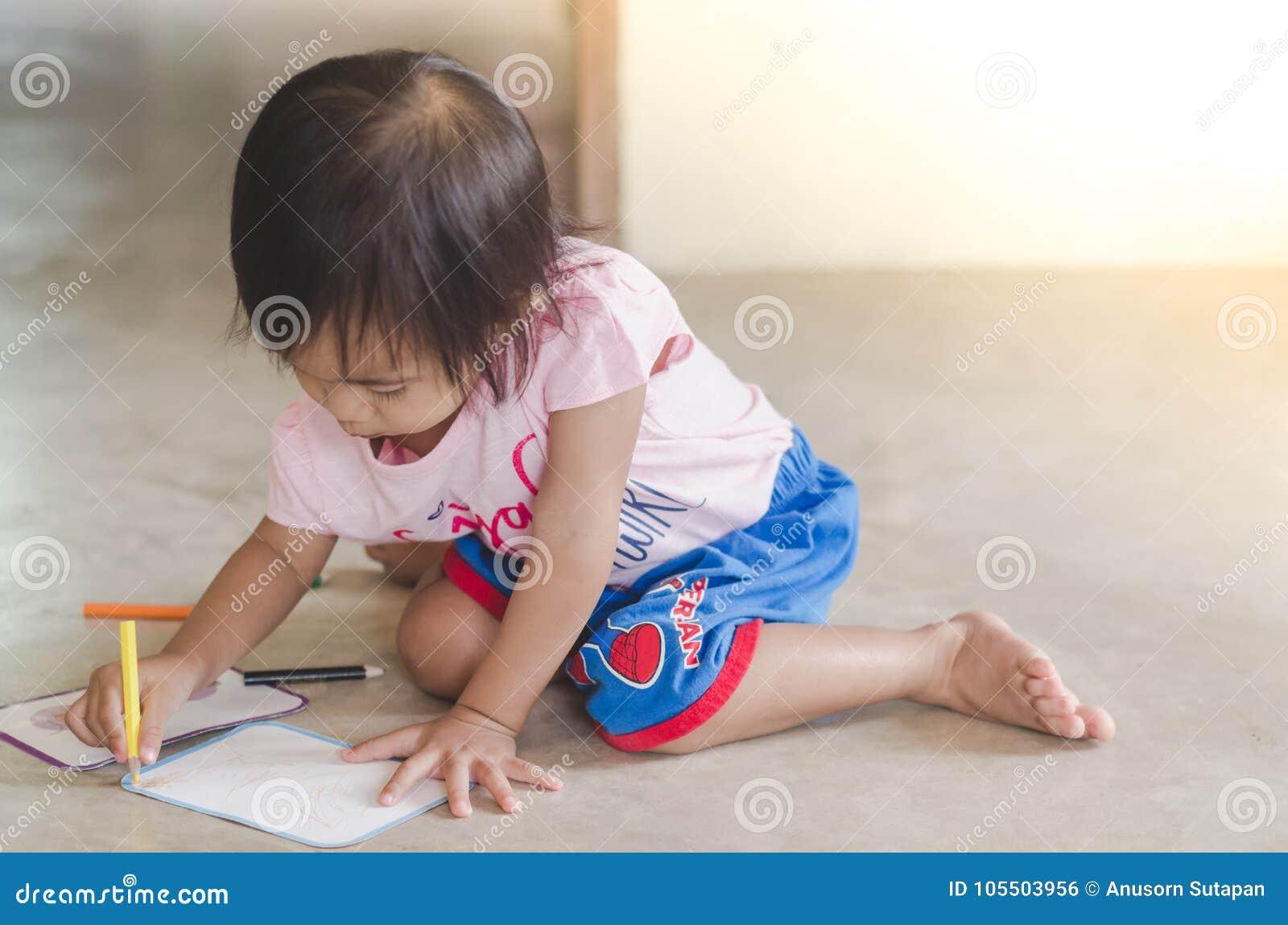 Dessin de petite fille avec le crayon de couleur sur le papier tandis que sittin
