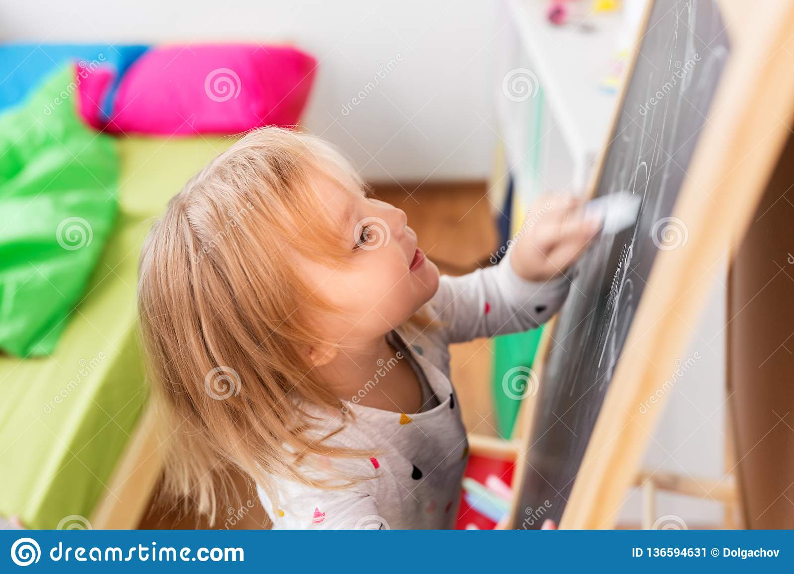 Dessin heureux de petite fille sur le panneau de craie à la maison