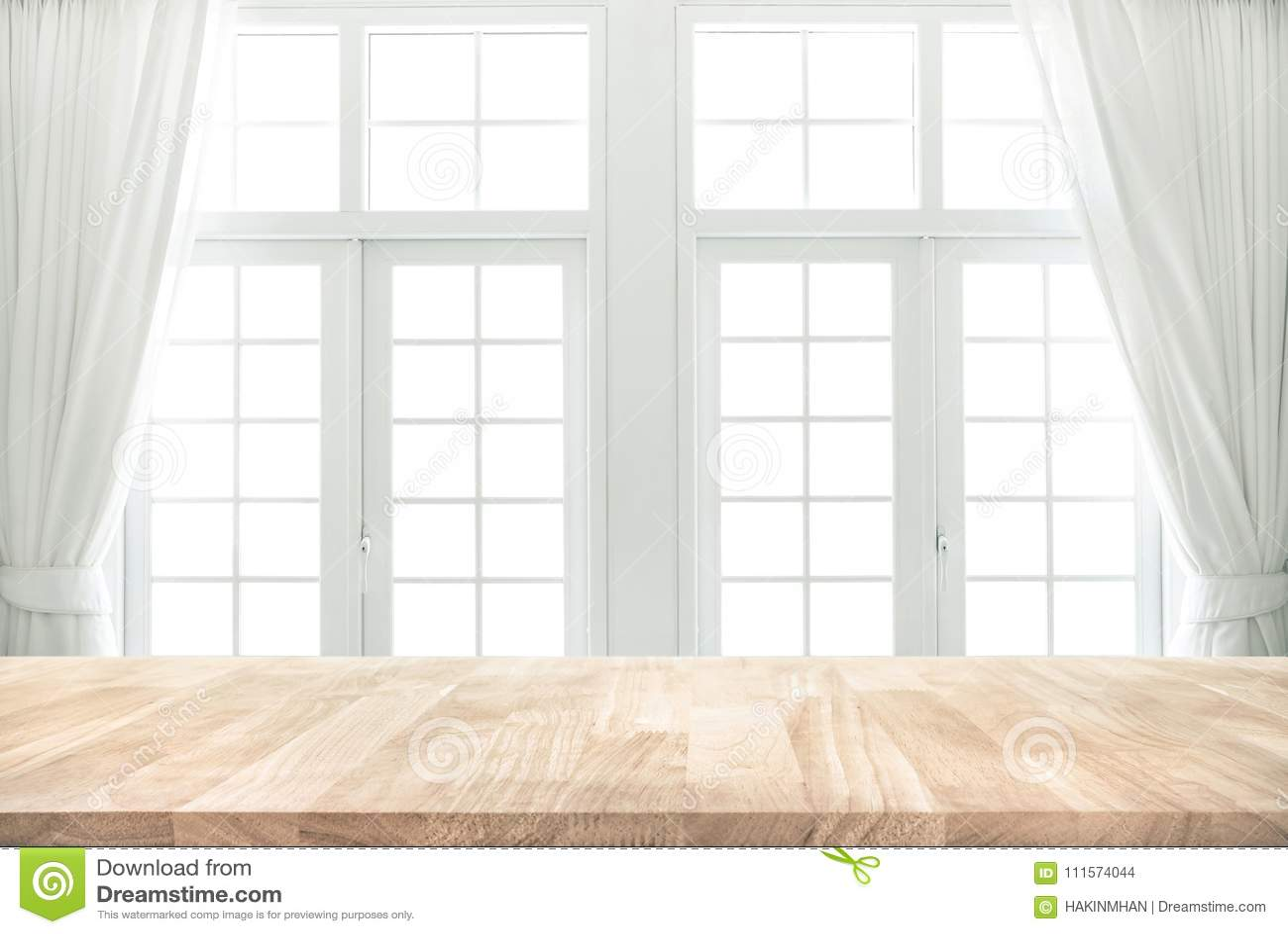 Dessus de table en bois sur la tache floue de la fenêtre blanche avec le fond de rideau