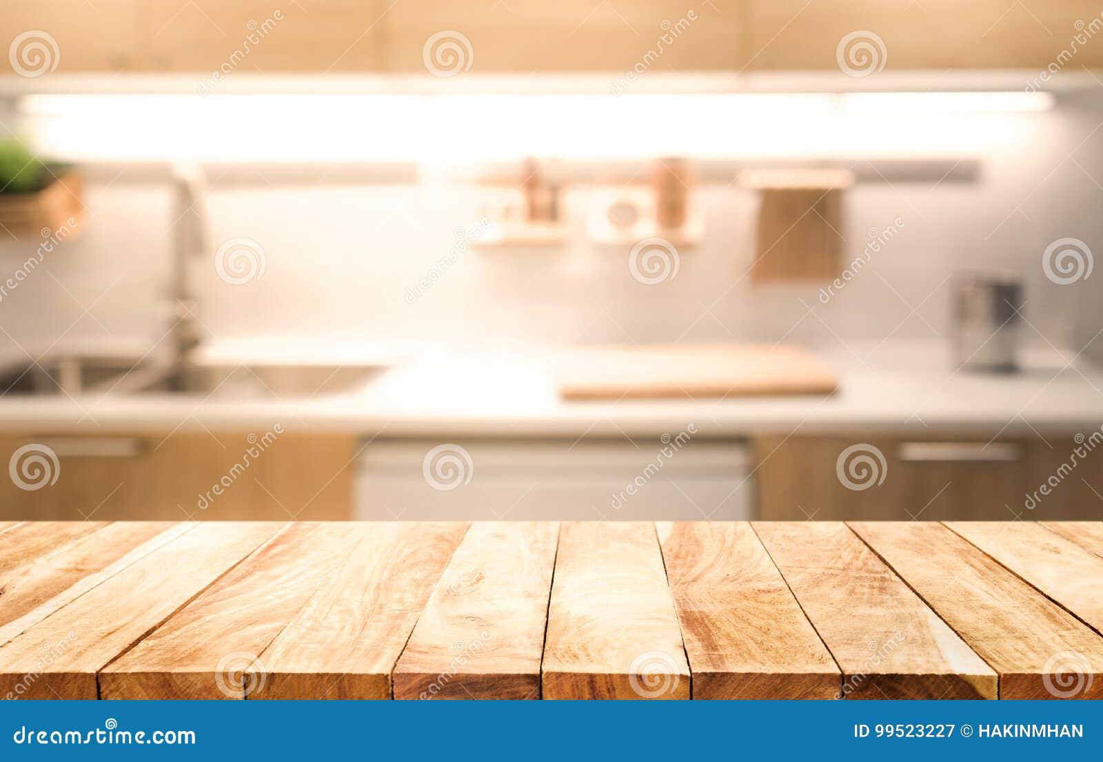 Dessus de table en bois sur le fond de pièce de cuisine de tache floue faisant cuire le concept
