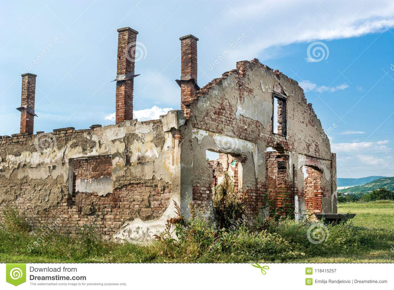 Destroyed old brick house without roof and with chimneys, broken windows, window frames, door and bricks
