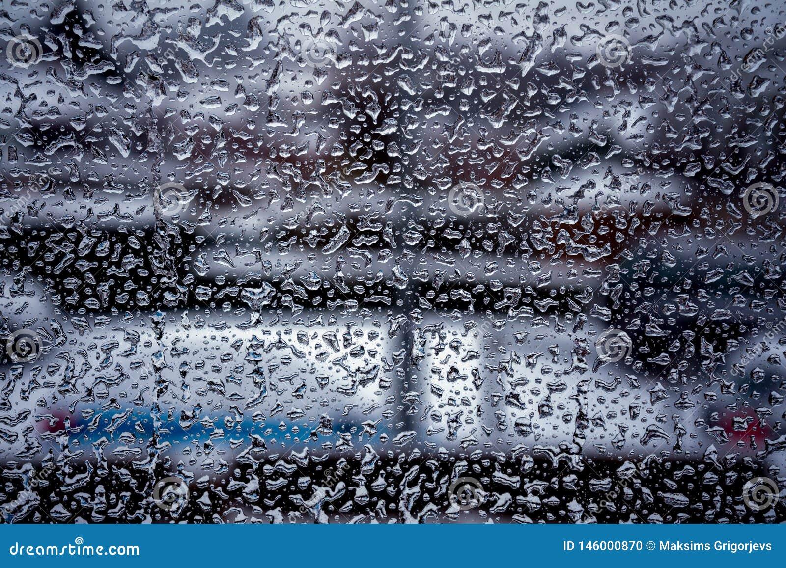 Deszcz krople na nadokiennym szkle ukazują się z chmurnym tłem