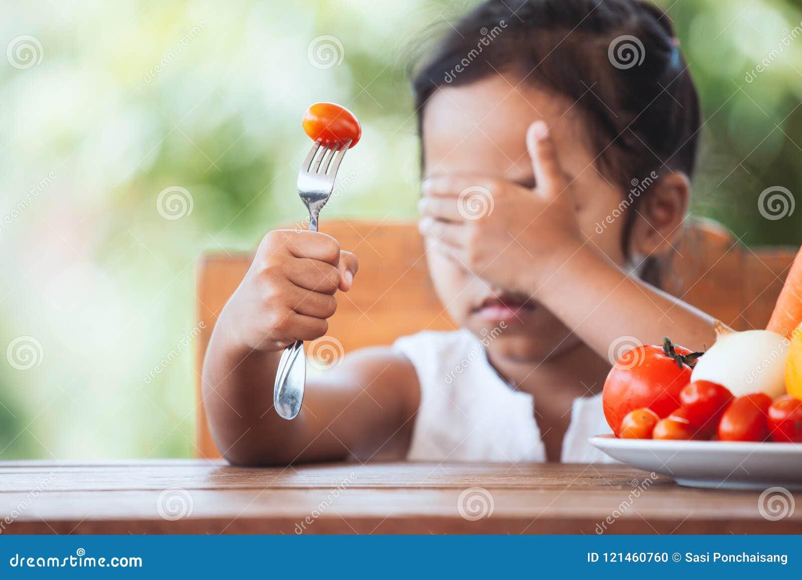 Det asiatiska barnet gillar inte att äta grönsaker