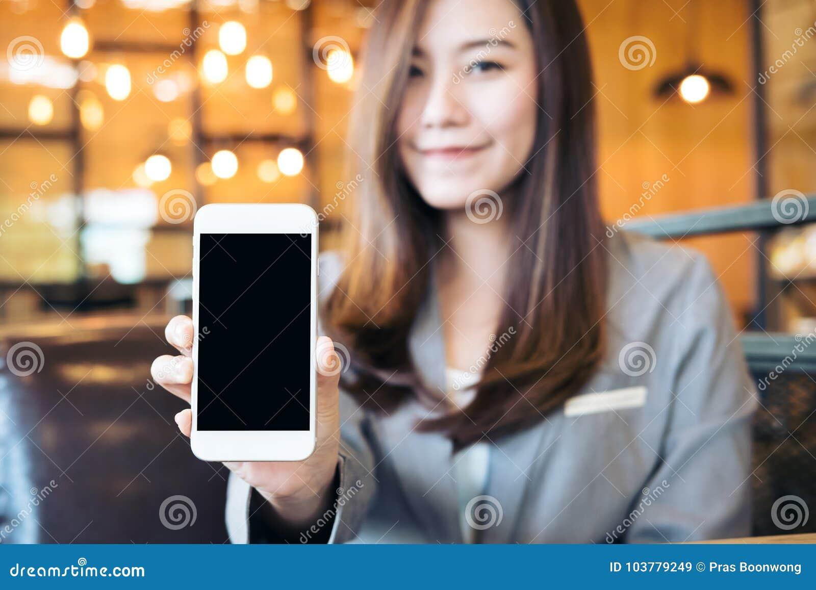Det asiatiska härliga innehavet för affärskvinnan och den vita mobiltelefonen för visning med mellanrumssvartskärmen och smiley v
