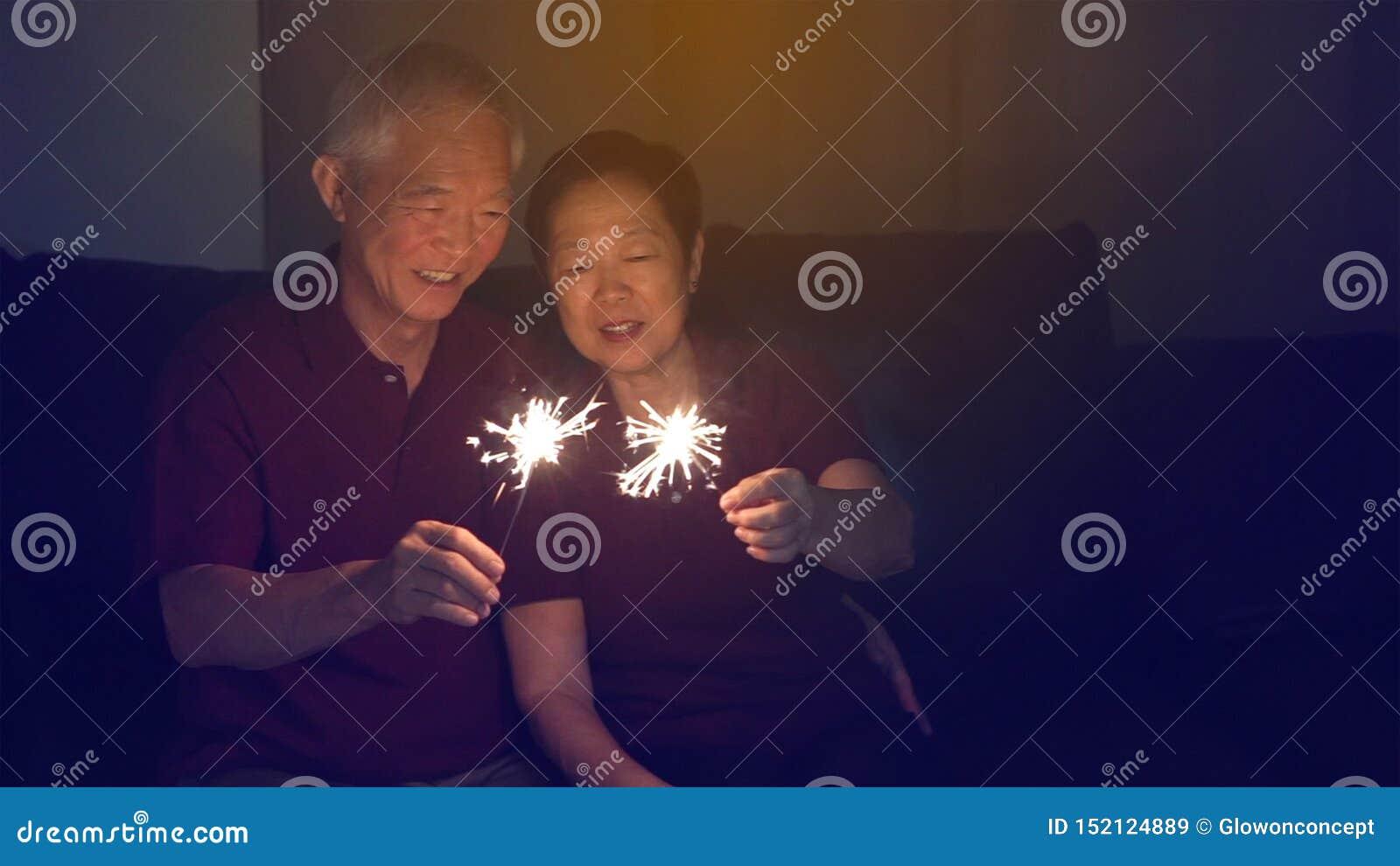 Det asiatiska höga paret som tillsammans firar mousserar hemma, fyrverkeri s